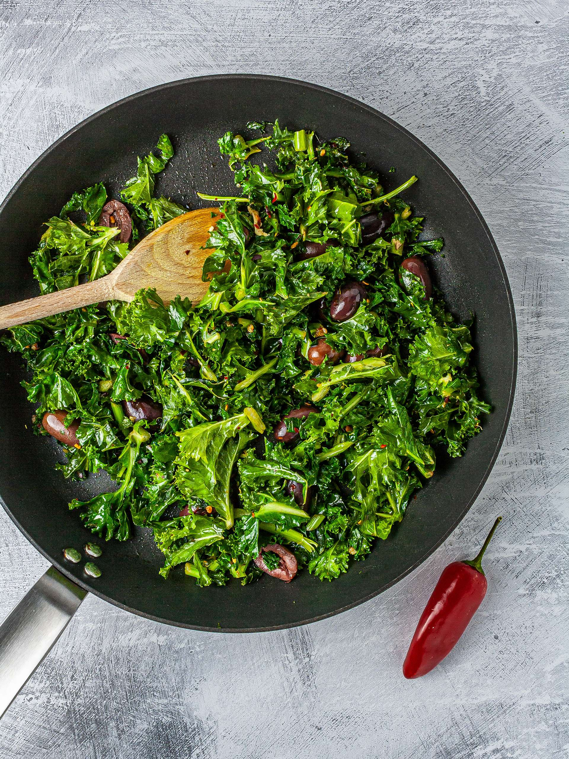 Kale cooked in a pan with chillies and olives.