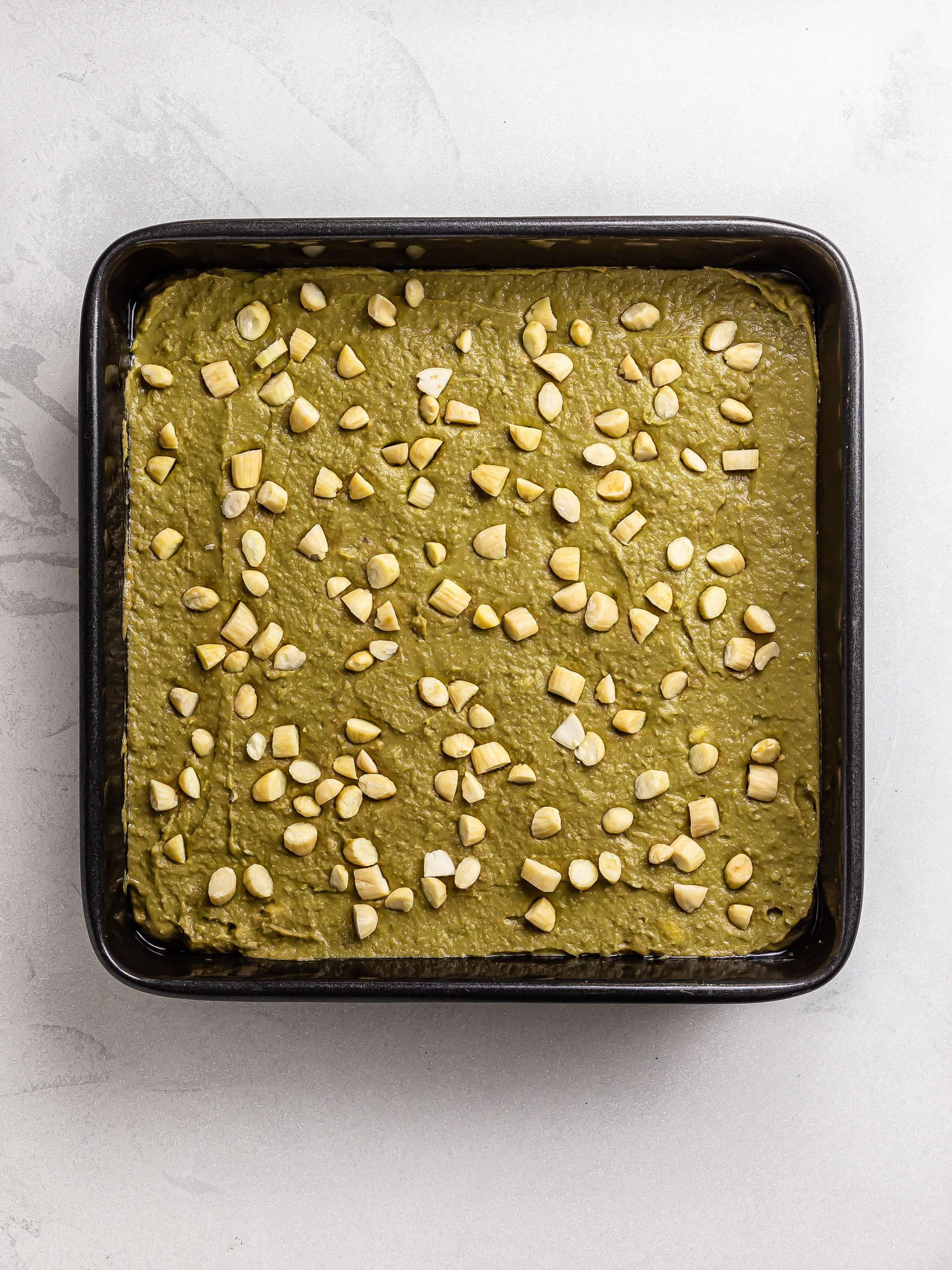 matcha brownies batter in a baking tin topped with almonds