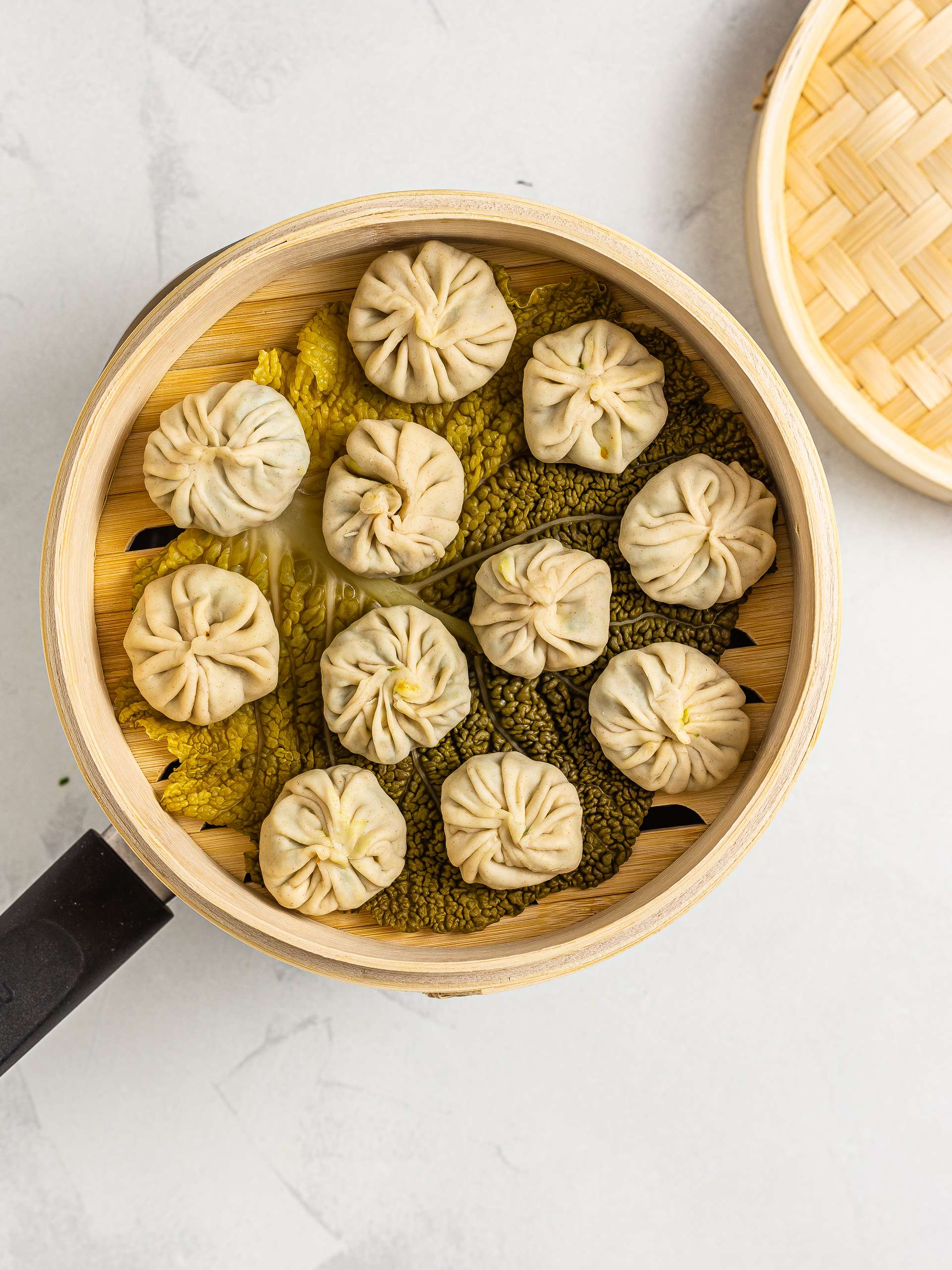 steamed momos dumplings in a steaming bakset