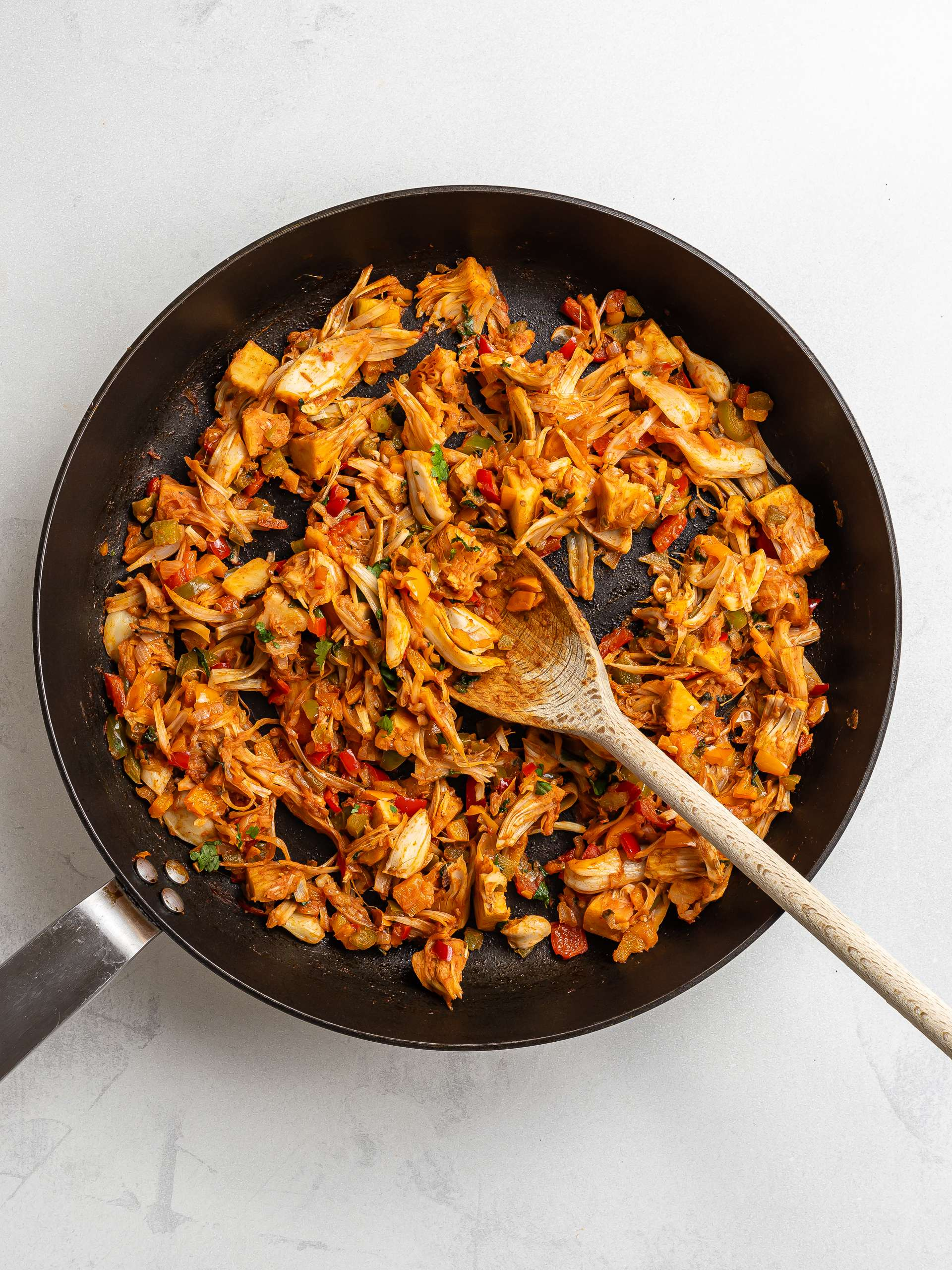 jackfruit and peppers cooked with enchilada sauce in a skillet