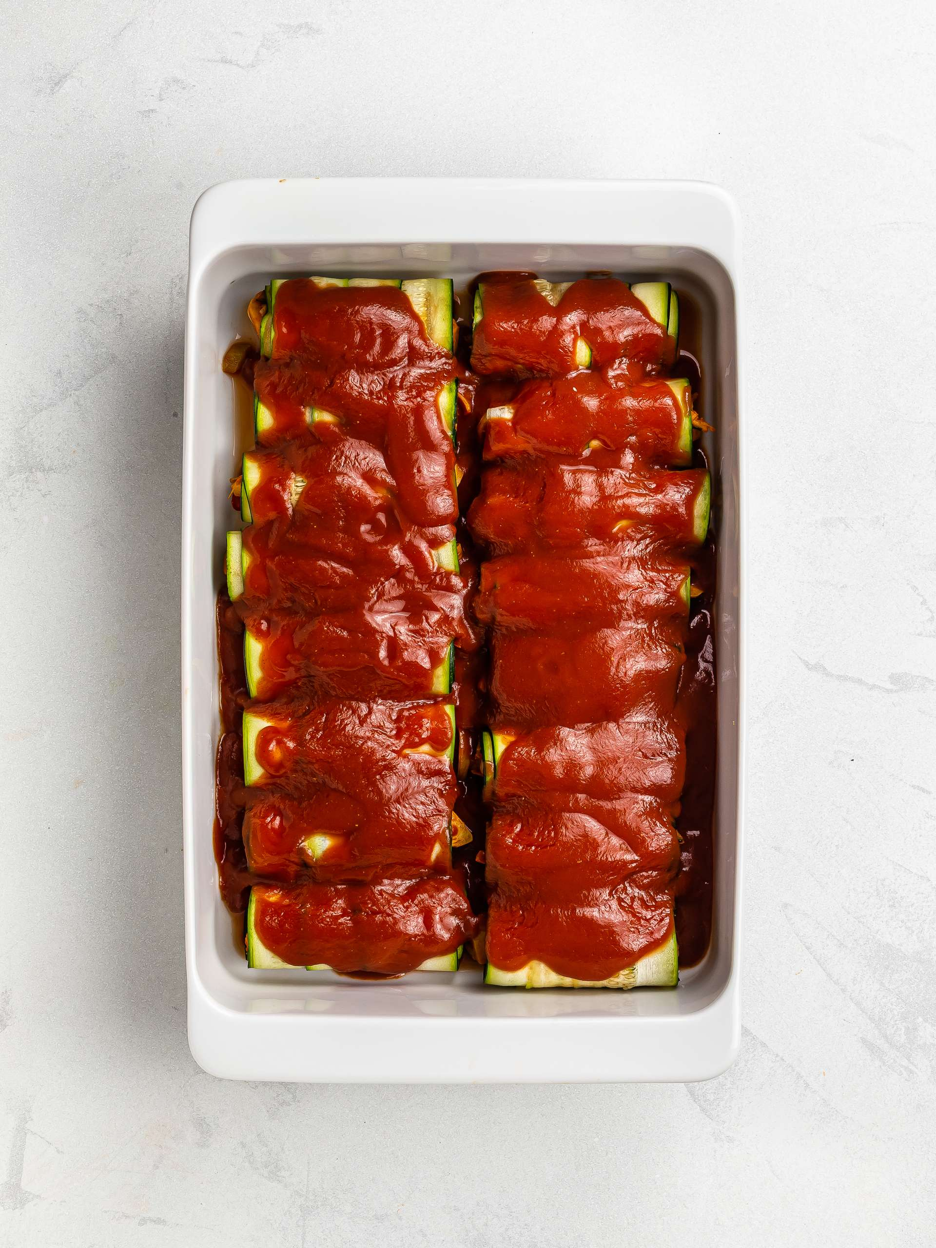 zucchini enchiladas in a casserole dish topped with tomato sauce