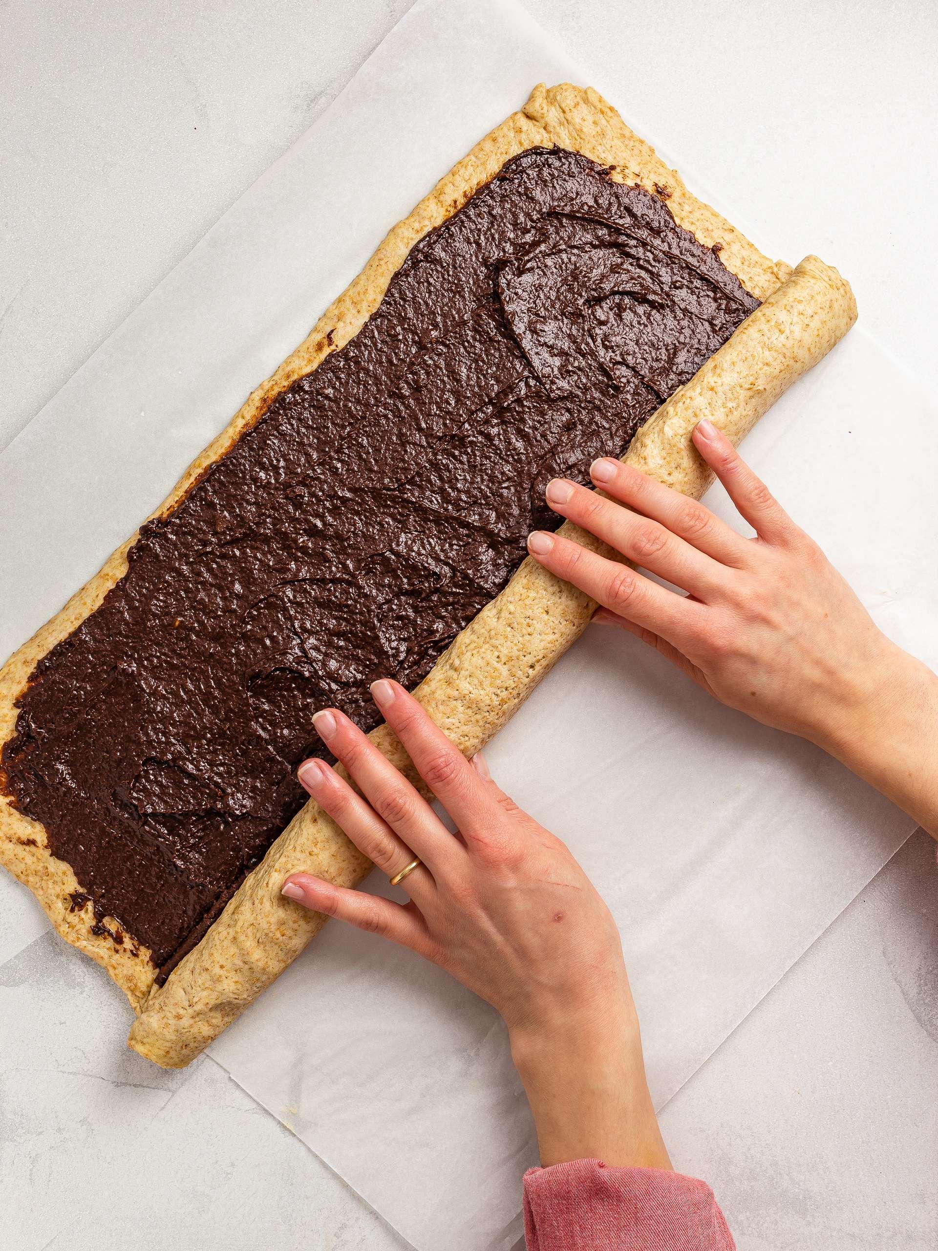rolling the krantz cake dough around the chocolate filing
