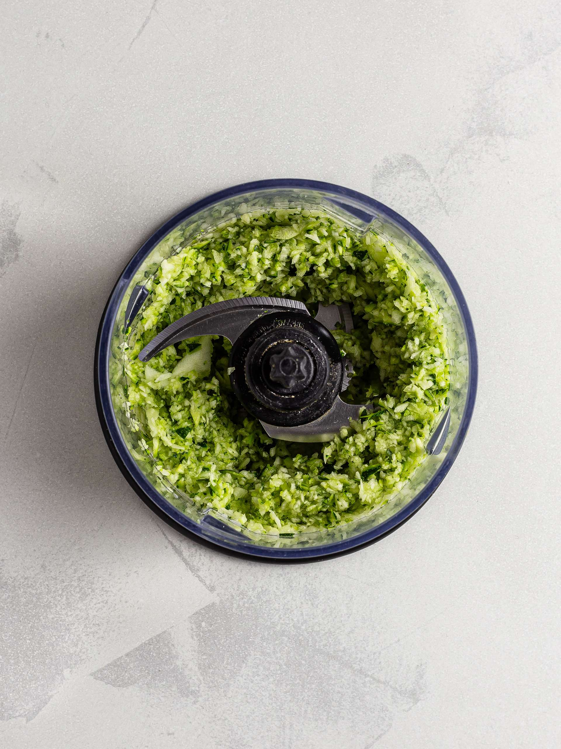 Grated zucchini in a food processor