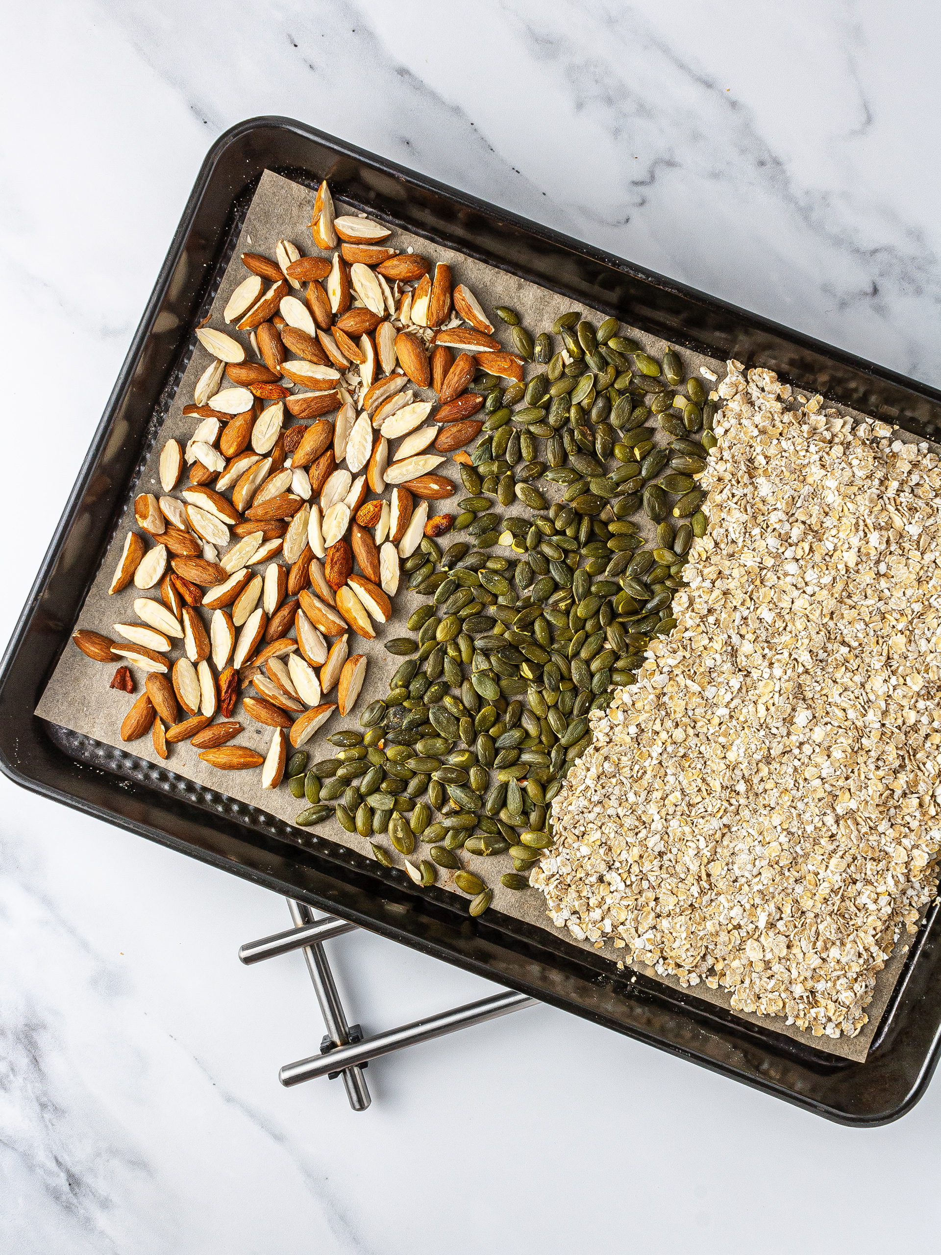 Oat flakes, almonds, and pumpkin seeds roasted in a baking tin.