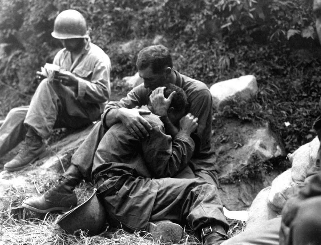 A grief stricken American infantryman whose buddy has been killed in action is comforted by another soldier. In the background a corpsman methodically fills out casualty tags, Haktong-ni area, Korea.  August 28, 1950.  Sfc. Al Chang. (Army) NARA FILE #  080-SC-347803 WAR & CONFLICT BOOK #:  1459