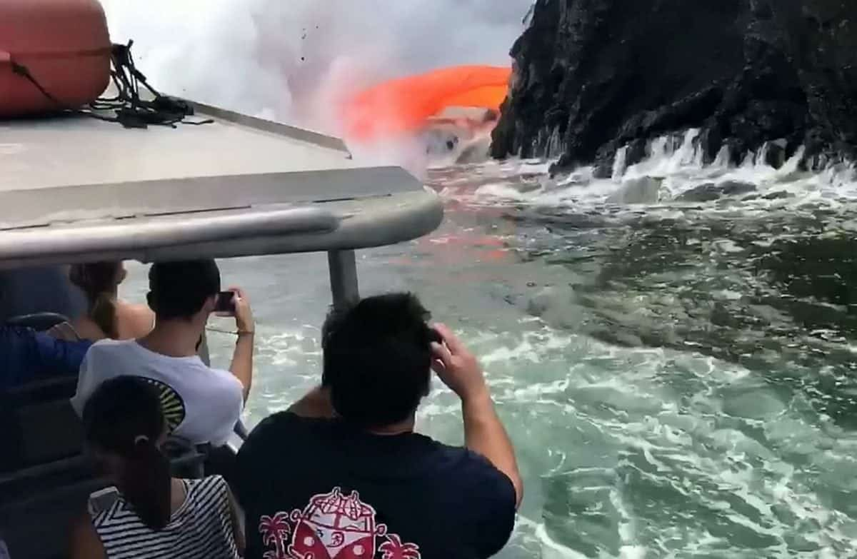 This is the spectacular moment tonnes of molten lava spew from a collapsed volcano into the sea - just yards from boat full of tourists. See SWNS story SWLAVA; Onlookers braved the choppy seas and deadly eruptions taking place at the Kamokuna lava delta in Hawaii since it collapsed on December 31. They were stunned when a red hot stream of 1000c lava suddenly crashed through the side of the black rock - causing an incredible hose pipe effect. Breath-taking footage shows the ''once-in-a-lifetime'' natural phenomenon as hot gunge pours into the sea - solidifying and producing thick clouds of steam. Tour operator Captain Shane Turpin, who shot the footage with guests on his Lava Ocean Tours ship, said: ''This was a real rare sight as the guests watched in awe.