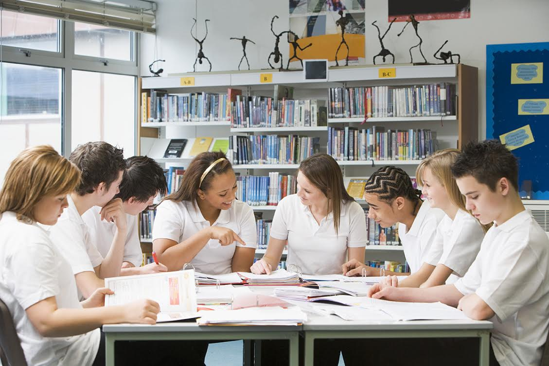 Schoolchildren studying in school library working together on project