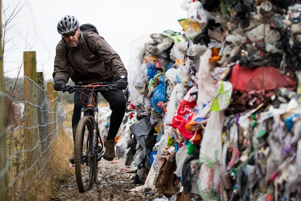 "Lee Tanner 49 rides past a mountain of waste such as food products, plastics and paper has been dumped on a cycle path between Biddulph and Brindley Ford, Staffordshire. February 01, 2017.  See NTI story NTIRUBBISH; Police are hunting ""industrial fly-tippers"" who dumped 50 huge blocks of compressed recyclable rubbish at a beauty spot popular with mountain bikers and walkers. Tens of thousands of discarded plastic bottles, bags and cardboard boxes which had been compacted into 10ft-high cubes were left strewn across the path. Cyclists and walkers were forced to squeeze past the stinking piles of trash after they were discovered on the route between Biddulph and Brindley Ford, Staffs., on Saturday (28/1).  Staffordshire Police and council officials are now investigating in a bid to find out who dumped the rubbish. Dog-walker David Rowe, 66, who discovered the waste, said: ""I walked my dog on Friday night and there was nothing there."