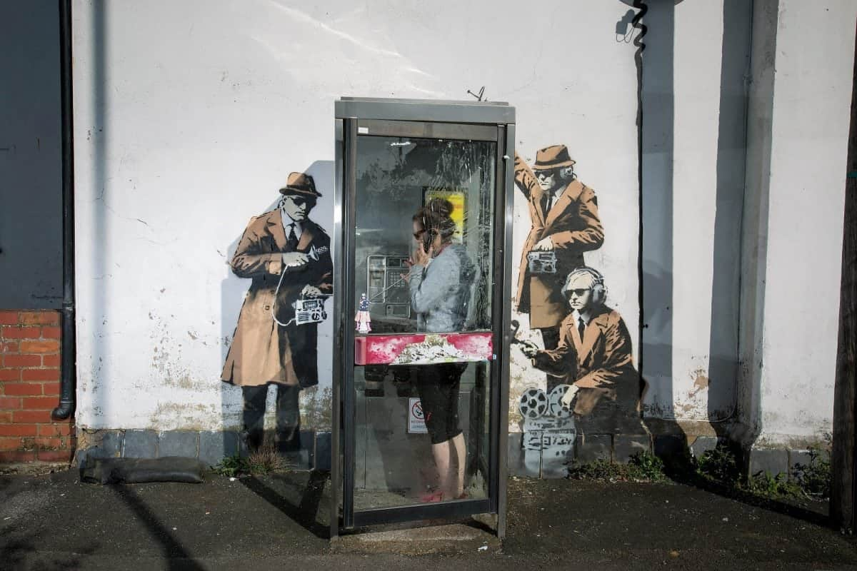 "FILE PHOTOS OF phone box which has been surrounded by new Banksy artwork in Cheltenham. 14th April 2014. See SWNS story SWBANKSY; A famous Banksy once valued at a million pounds which ""fell"" off a wall appears to be for sale on Facebook. The elusive artist created 'spy booth' depicting three 'spooks' snooping on a phone box with listening devices near GCHQ in Cheltenham, Glos., in 2014. But it was reduced to a pile of rubble when builders worked on the wall above the artwork and it collapsed last summer. Building owner David Possee took the bits to the council for safekeeping, but yesterday (Weds) the broken pieces appeared for sale on Facebook."