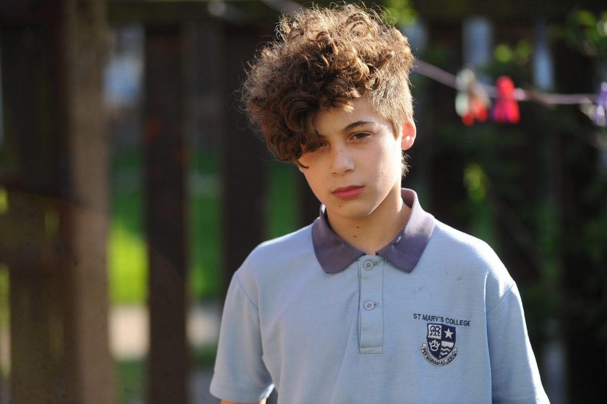 "Haman Karim, 13, has been kept in isolation for two months at St Mary's College because of his haircut. See Ross Parry story RPYPERM; An angry mum claims her teenage son has been taken out classes after having his hair PERMED to copy his rapper idol. Haman Harim, 13, had his head shaved at the sides and an 80s-style perm on top so he could look like teen rapper Little T. But mum Sharon Coxall says he was then excluded from normal classes because teachers claimed his retro hairstyle was affecting his education. Sharon, 51, hit out at the decision by teachers to put him in 'pastoral' care over his hairdo two months ago. And she claims that even though the shaved sides have now grown out the school are still keeping the Year Nine pupil 13 out of mainstream classes. The mum-of-six blasted: ""It's a bit over the top. How does his hair affect his education? That's what is important."""