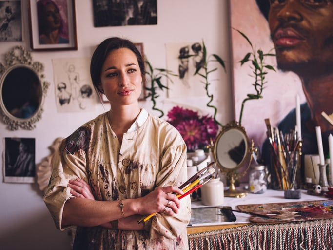 Beautiful young woman artist looking away thoughtfully with her arms crossed and holding some paintbrushes in her creative studio wearing an old-fashioned artist's smock which is covered with paint marks