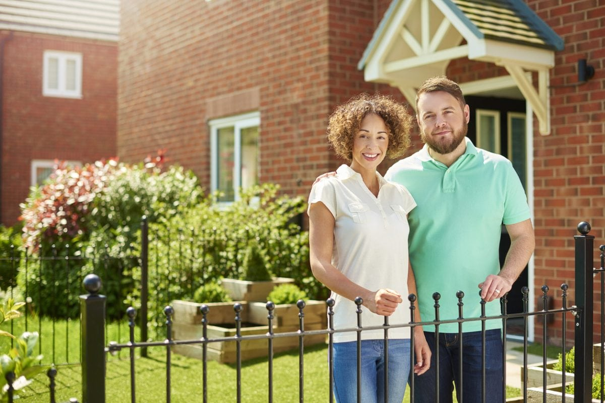 a mid adult couple stand at the front of their house and smile to camera . They are a mixed race couple , and their house is part of a new build housing development.