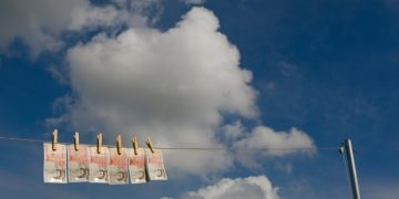 UK currency - new £50 notes - 'drying' on a washing line on a Summer's day. Symbolising money laundering.