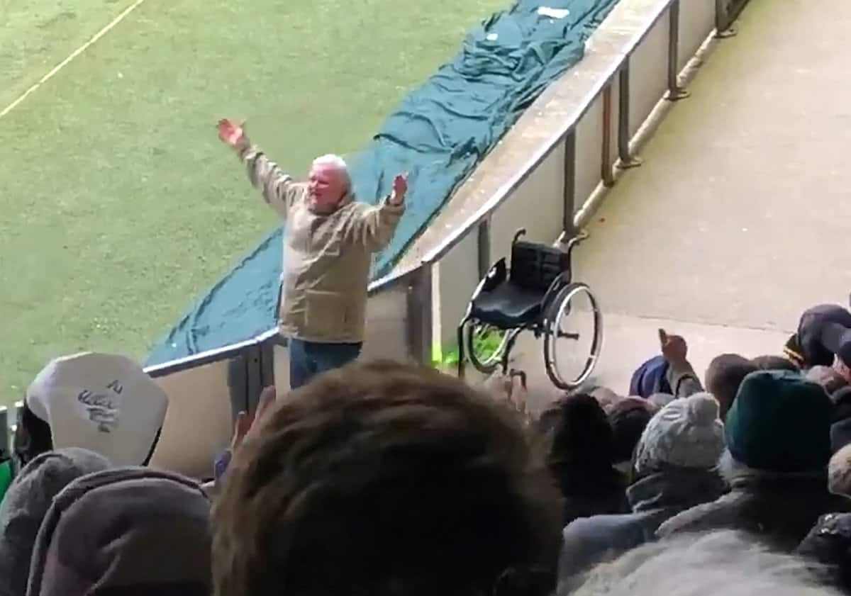 This video shows the moment a football supporter had a real-life Little Britain moment - when he rose from his wheelchair to start celebrating. See SWNS story SWFAN; Sports reporter Jak Ball filmed the fan wheeling his chair up and down the side of the pitch before he stunned the crowd by jumping out of it in delight and waving his arms aloft. The 'miracle' was reminiscent of the Little Britain TV show, where the character Andy Pipkin feigns the need for a wheelchair to his carer, Lou Todd! It is not known what disabilities the supporter may suffer, but Jak, who works for the Plymouth Herald, said he couldn't believe what he was seeing.