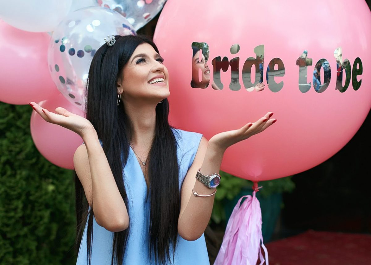 Happy young beautiful brunette bride to be with dark hair and silver crown smiling and gesturing spread out her hands in joy on bachelorette pink party balloon background.