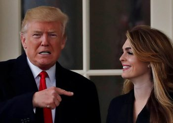 FILE PHOTO: U.S. President Donald Trump reacts as he stands next to former White House Communications Director Hope Hicks outside of the Oval Office as he departs the White House for a trip to Cleveland, Ohio, in Washington D.C., U.S., March 29, 2018. REUTERS/Carlos Barria/File Photo