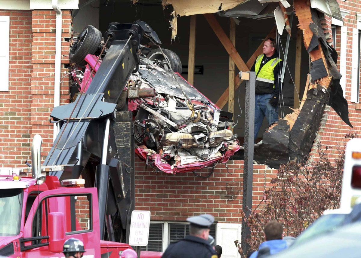 A Porsche is removed form the second story of a building after the convertible went airborne and crashed into the second floor of a New Jersey commercial building early Sunday, killing both of the car's occupants, in Toms River, N.J. (Ed Murray/NJ Advance Media via AP)