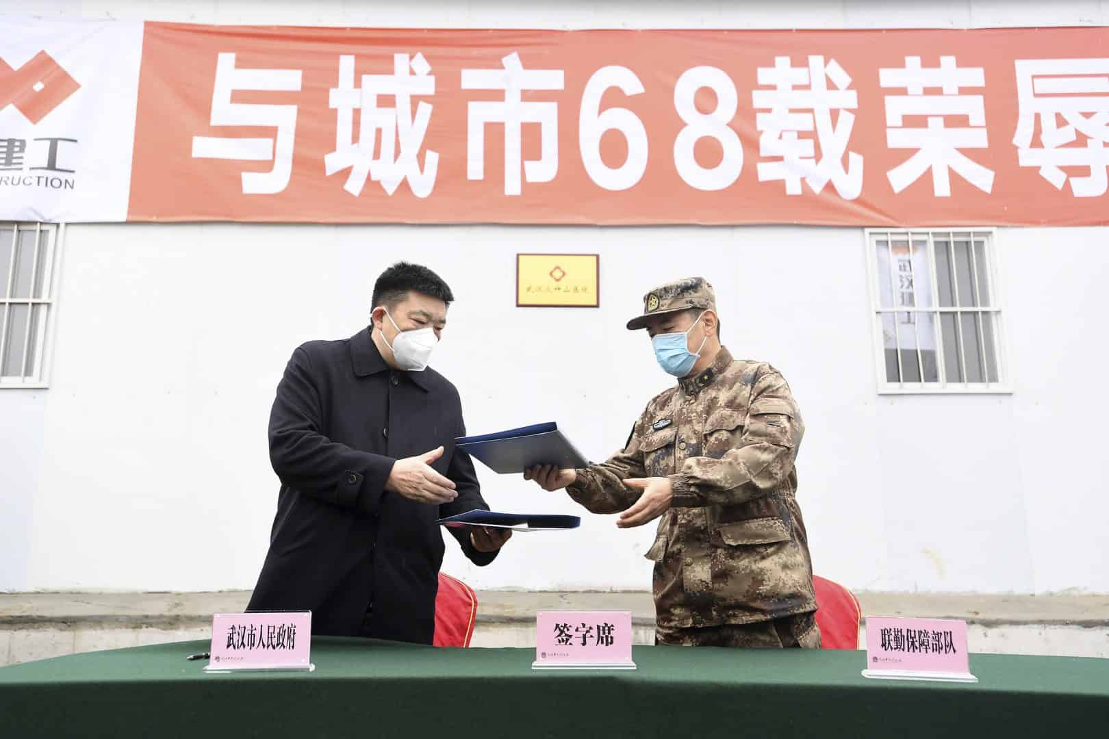 Zhou Xianwang, left, the mayor of Wuhan, exchanges documents with Bai Zhongbin, right, deputy commander-in-chief of China's People's Liberation Army (PLA) Joint Logistic Support Force, during a handover ceremony at the Huoshenshan temporary field hospital (AP)