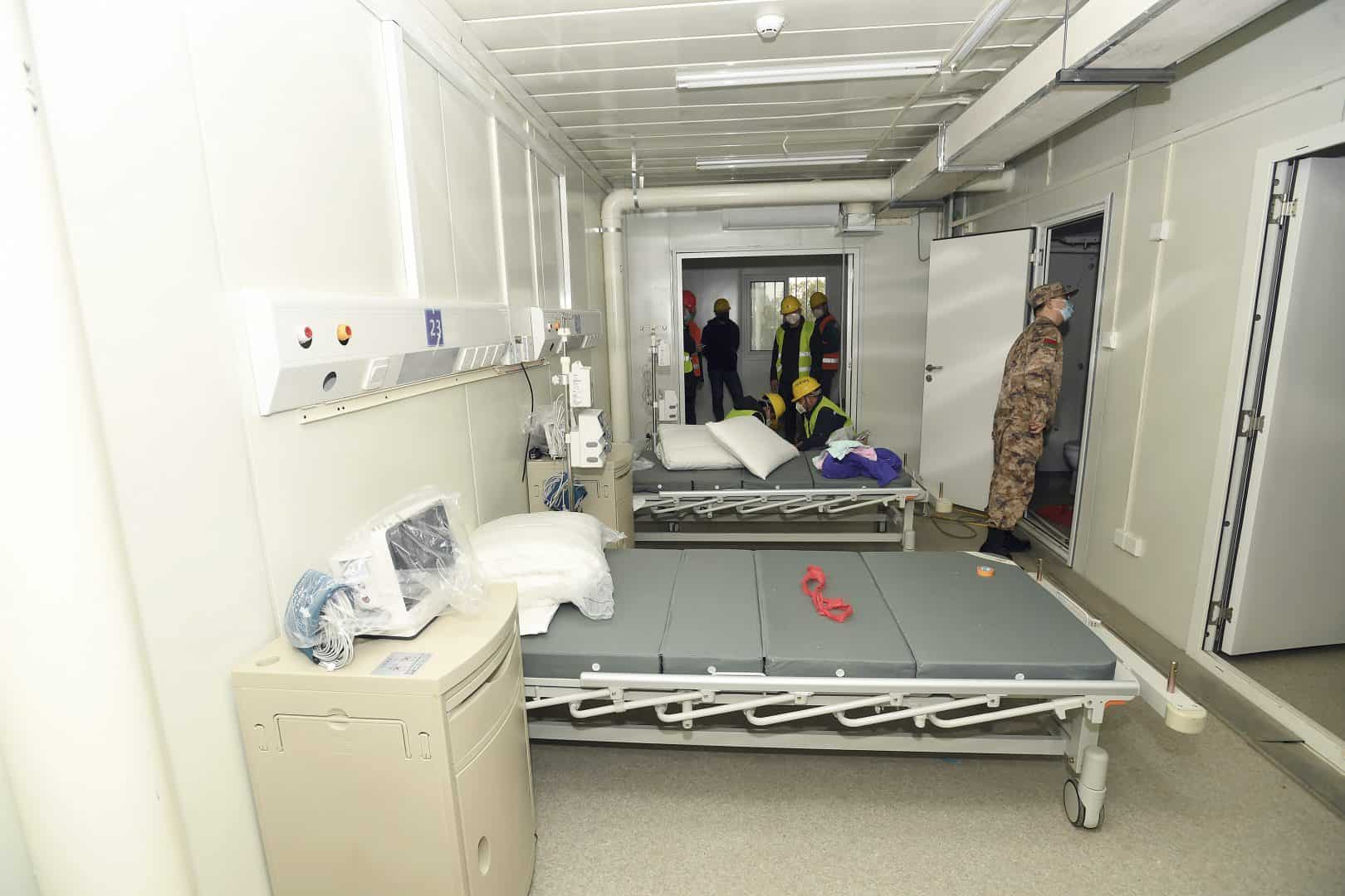 A Chinese army medic looks at a patient room at the Huoshenshan temporary field hospital in Wuhan (Chinatopix/AP)