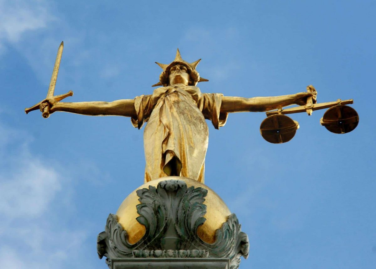 View of the gold statue of the figure of justice, holding scales and a sword, on top of the Central Criminal Court, also referred to as Old Bailey, in central London.