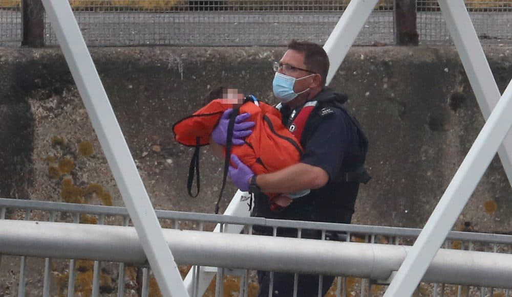 A Border Force officer carries a young child as a group of people thought to be migrants are brought into Dover, Kent, on a Border Force vessel following a number of small boat incidents in the Channel earlier today.