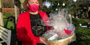 Carer Norma Kirby at Charnley Fold Day Centre in Bamber Bridge near Preston with a Christmas hamper delivered by Lottery winner Natalie Cunliffe. Credit;PA