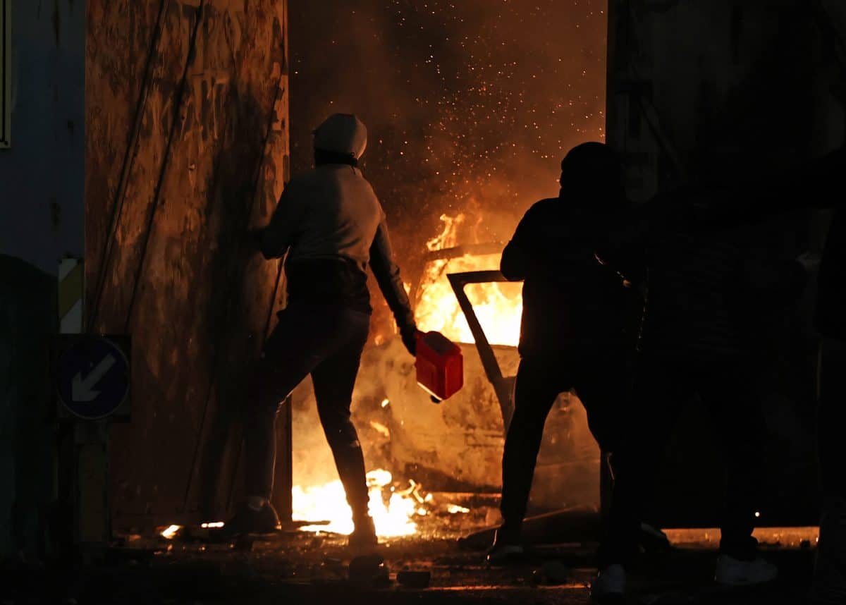 A nationalist throws a petrol canister the Peace Gates in Lanark Way, Belfast during further unrest in Belfast. Picture date: Wednesday April 7, 2021.
