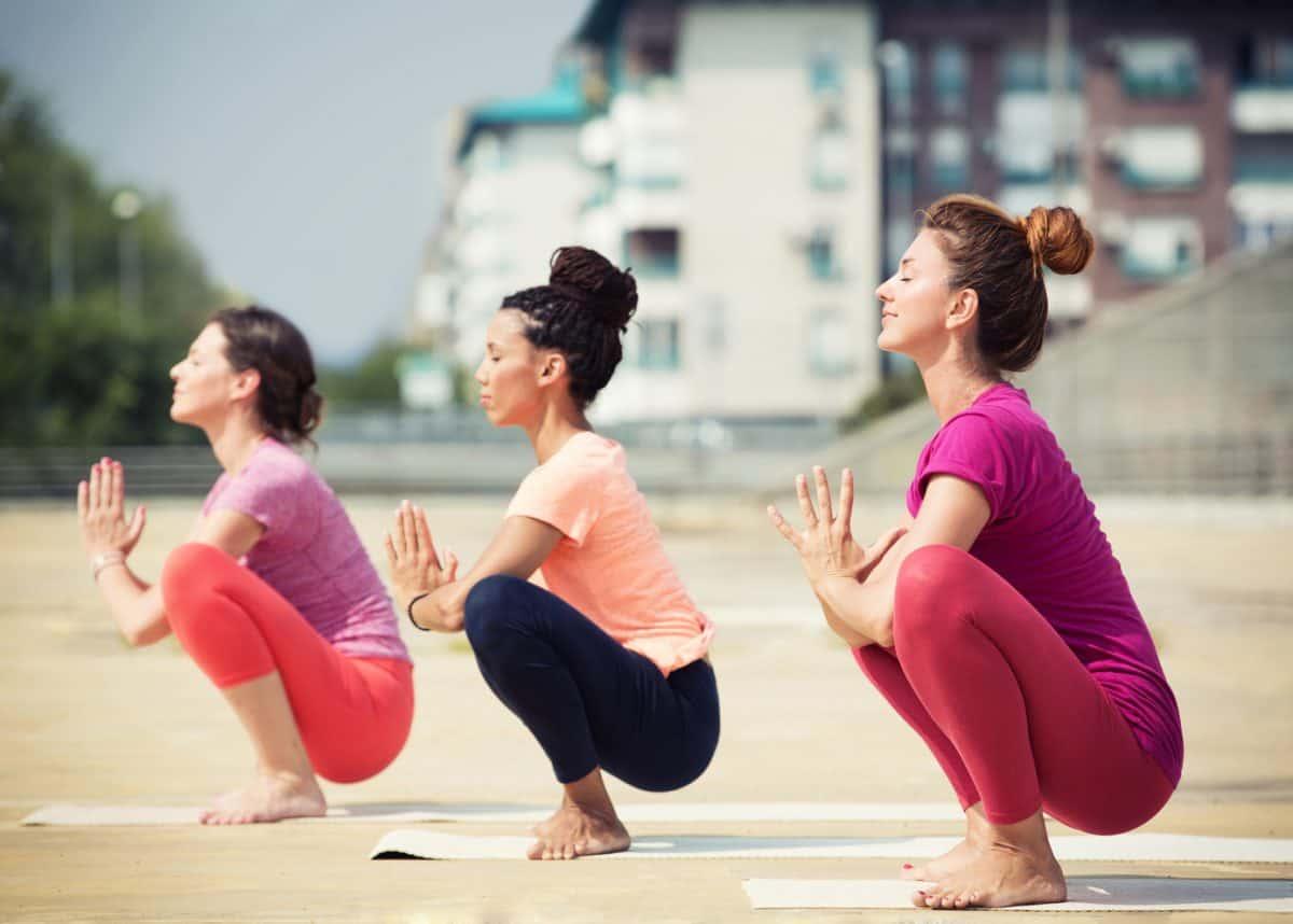 Beautiful women doing yoga outdoors in an urban neighbourhood
