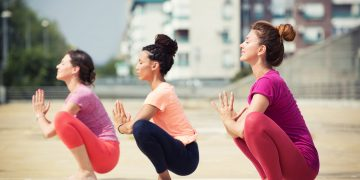 Beautiful women doing yoga outdoors in an urban neighbourhood