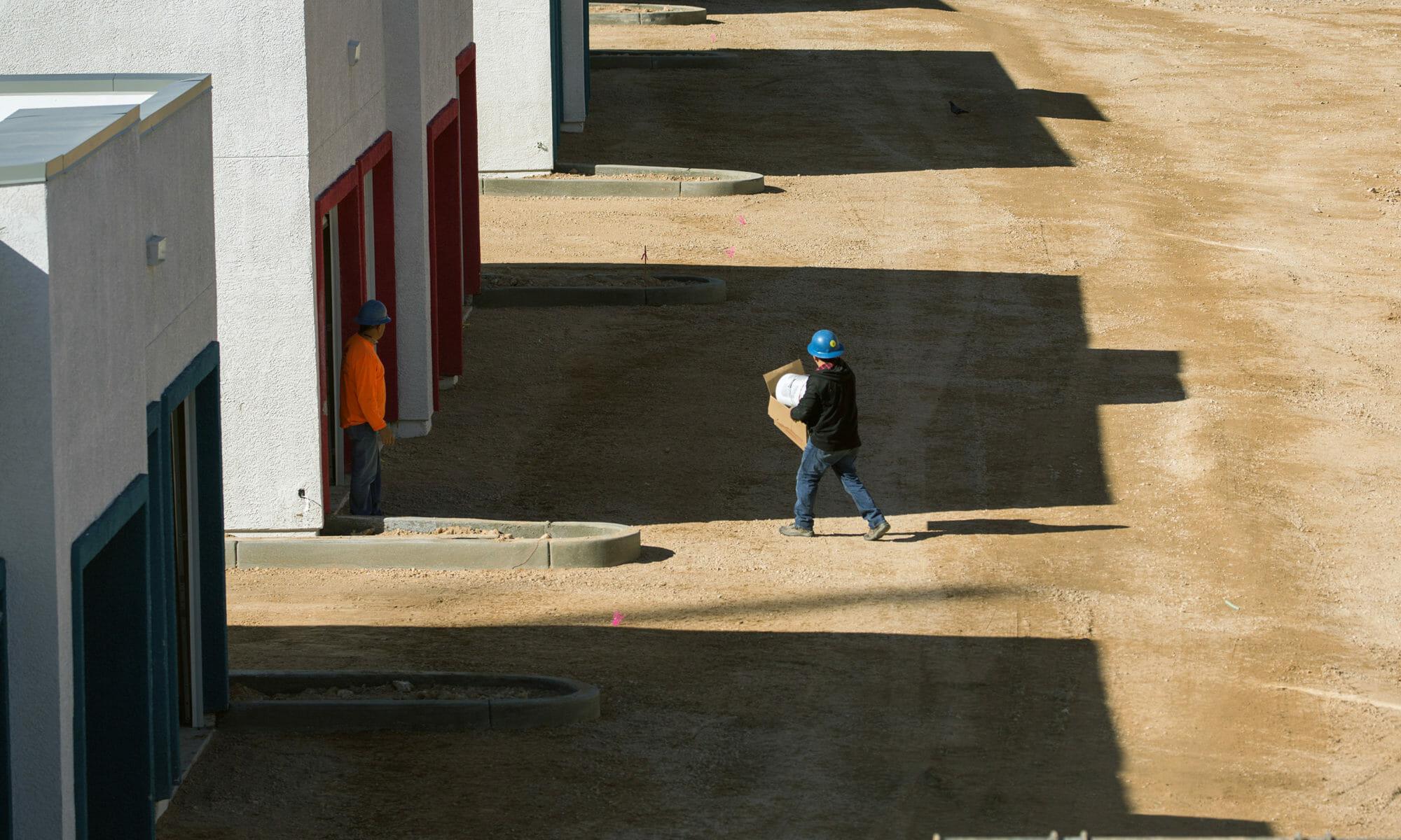 A workman walking towards an apartment building under construction