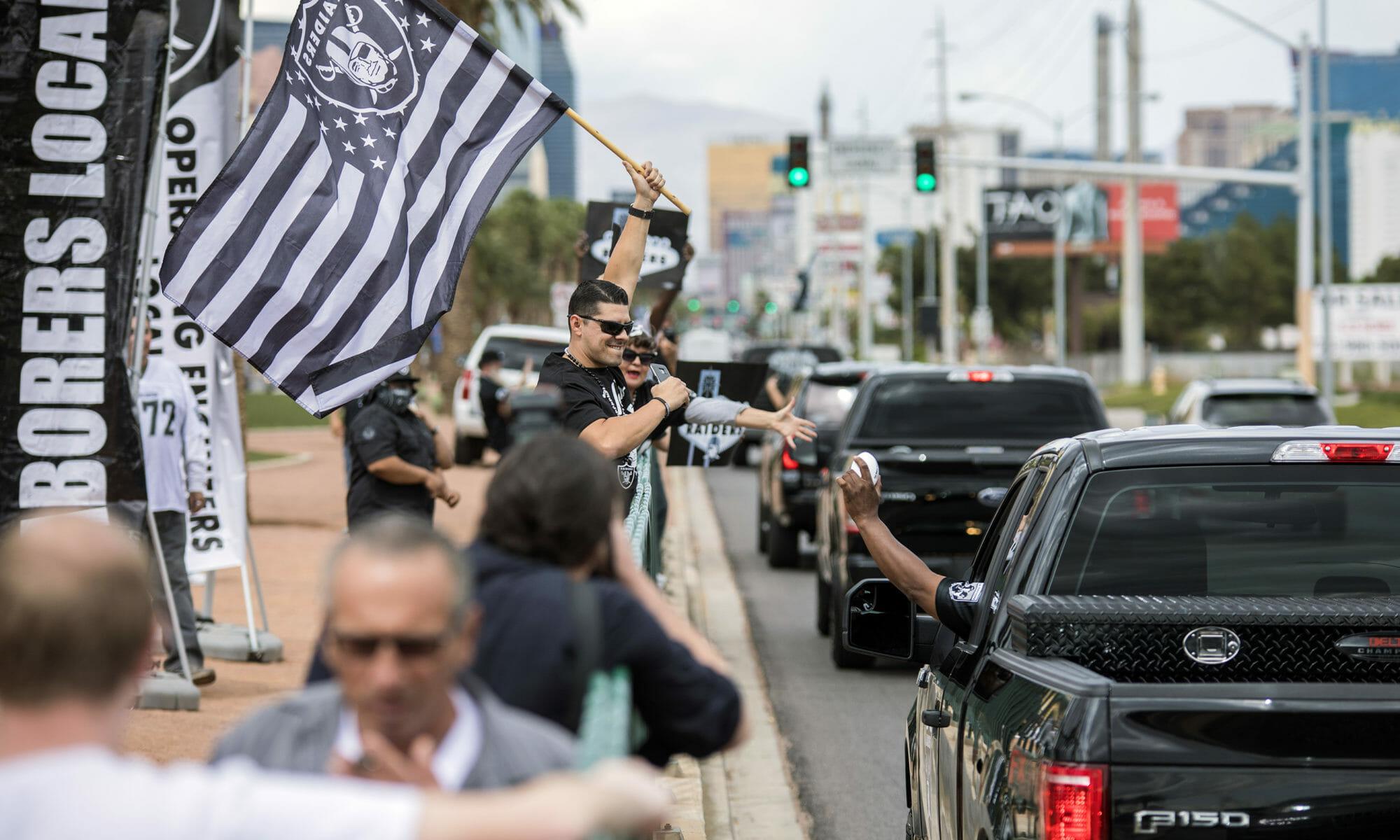 A man waiving a Raiders flag on a sidewalk