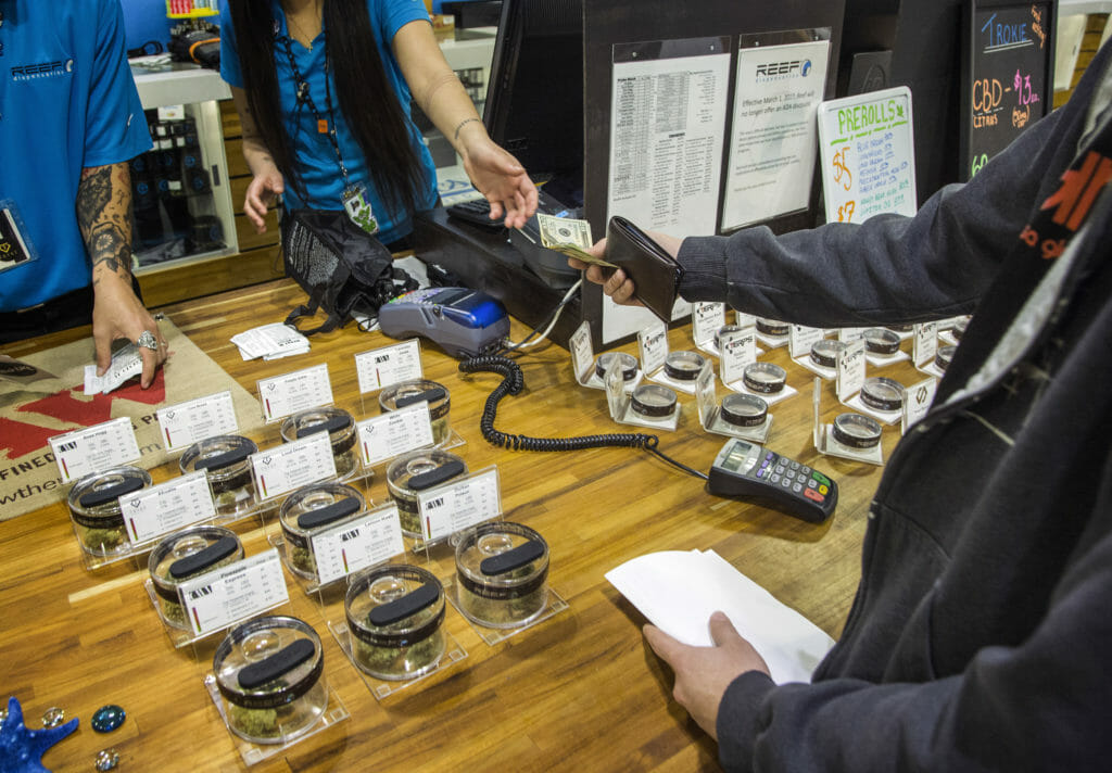 A customer and retailer exchanging money at a cannabis retailer