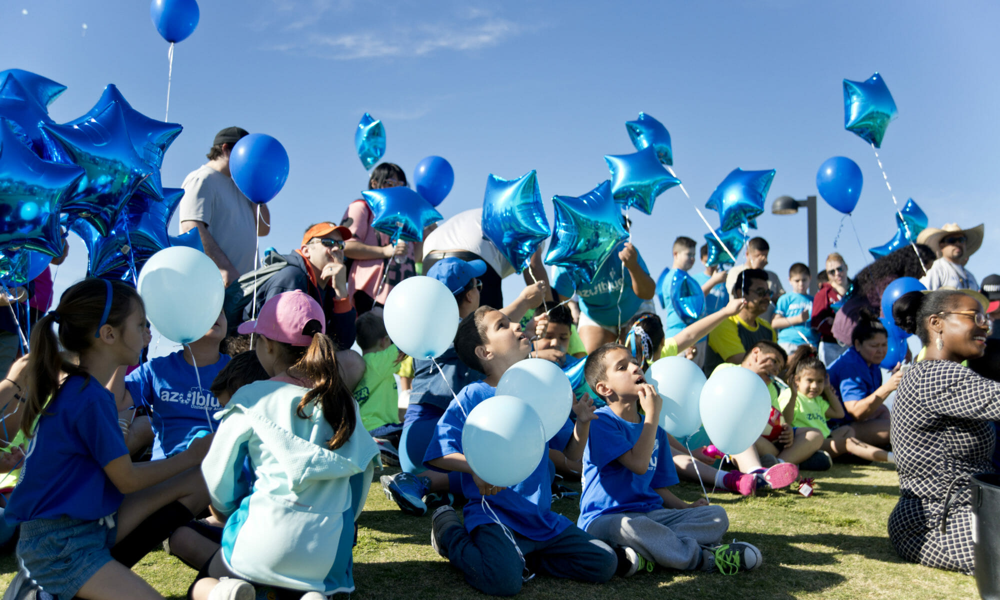A group of people releasing blue balloons