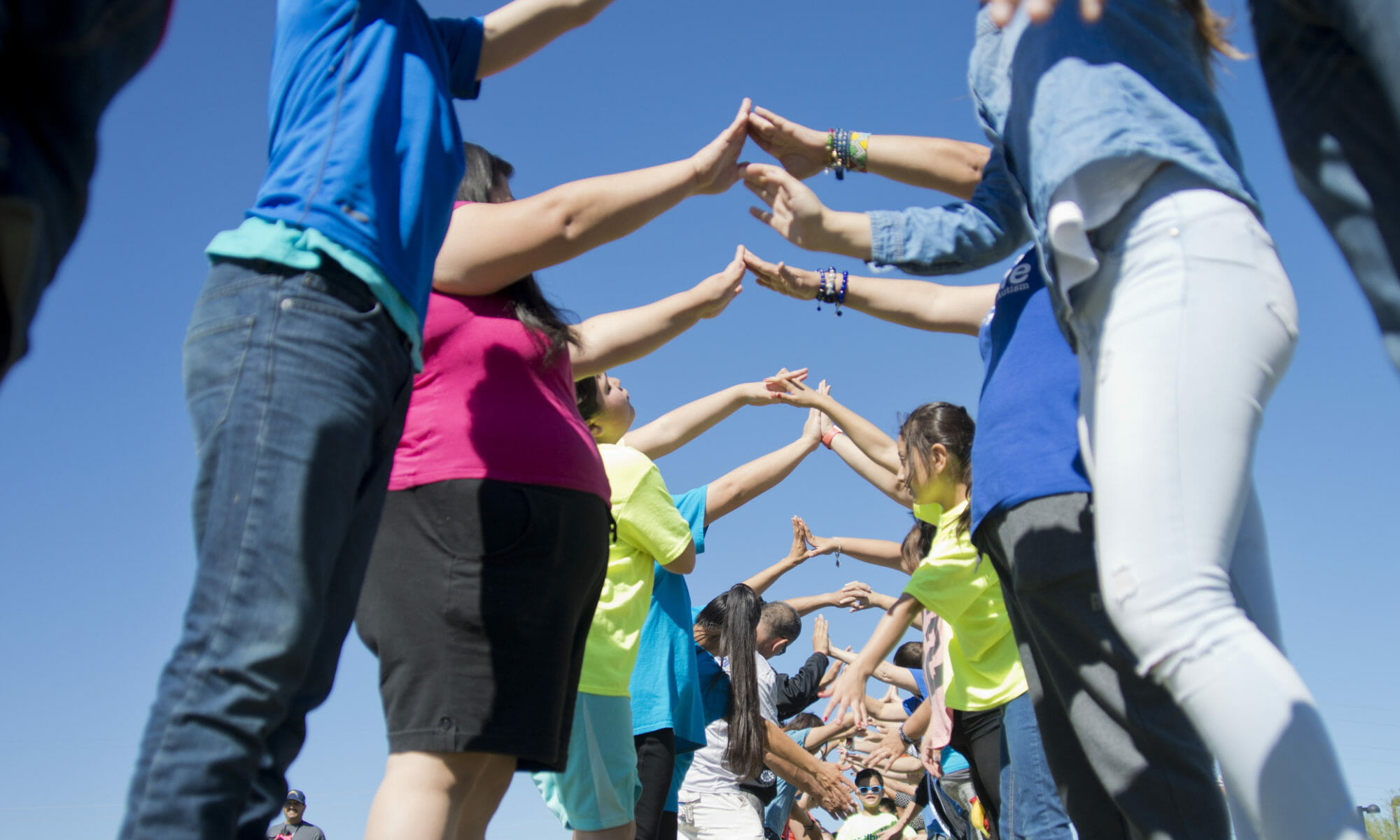 A group of adults holding hands to create a tunnel for kids to run through