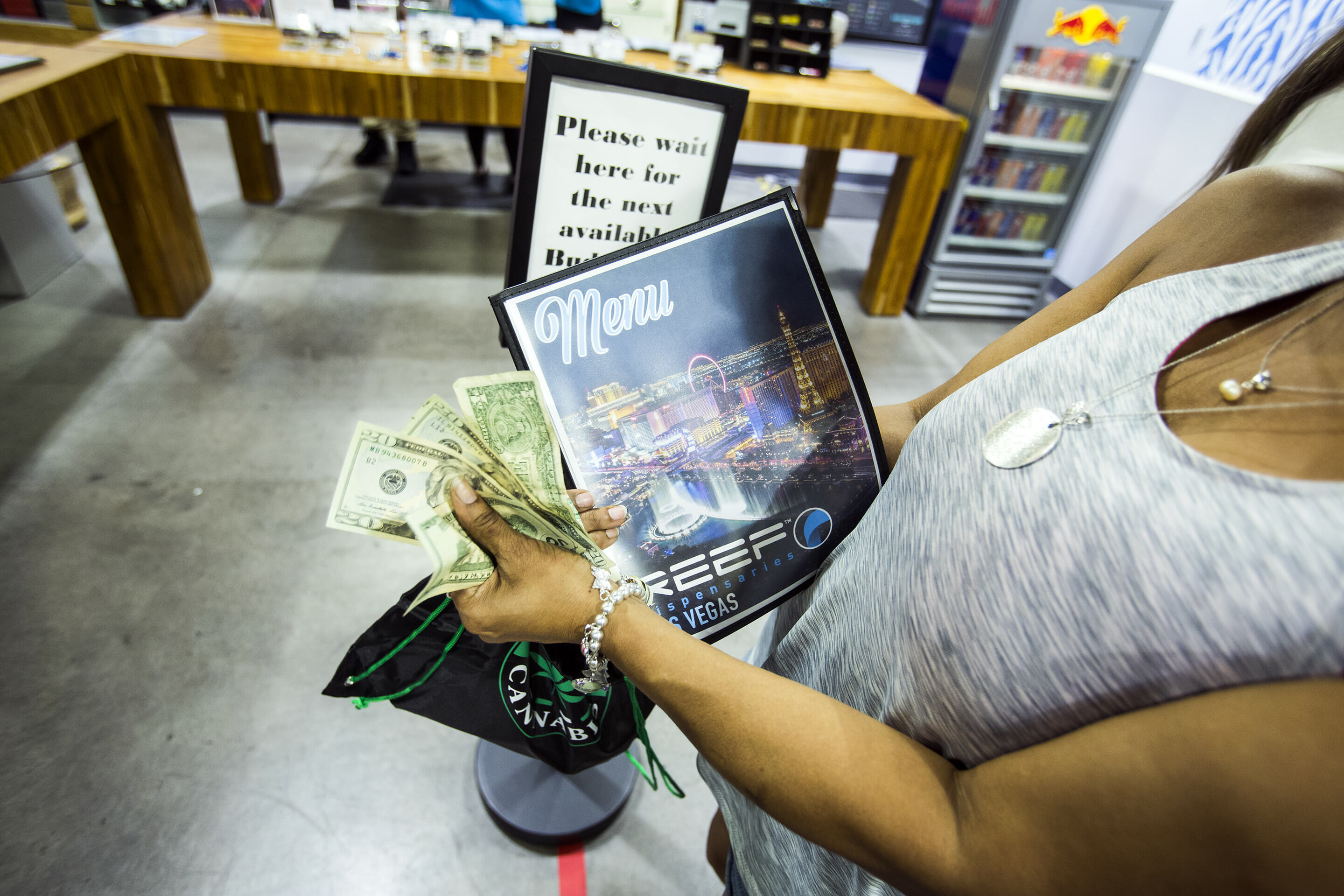 Woman holding money at dispensary