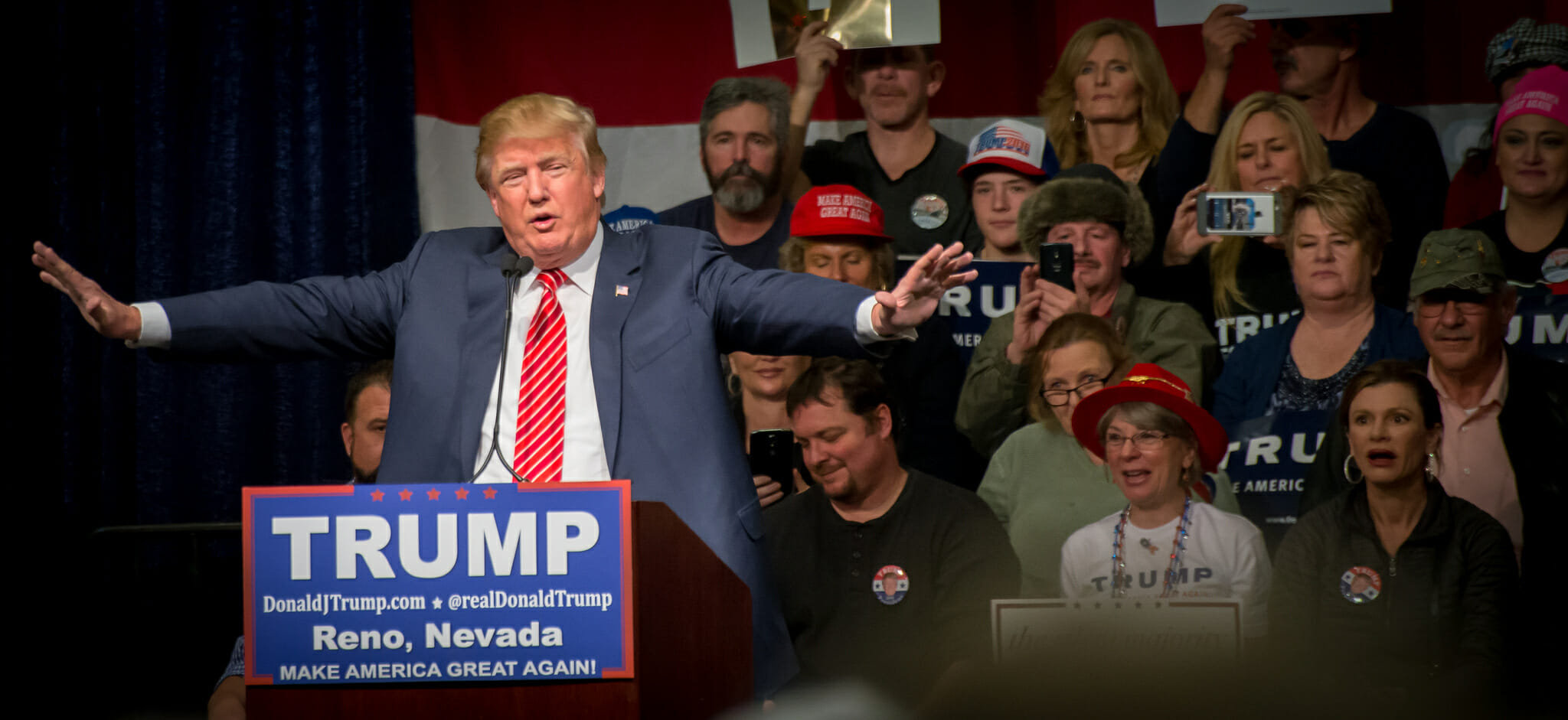 Then-candidate Donald Trump at the podium in a blue jacket and red tie.