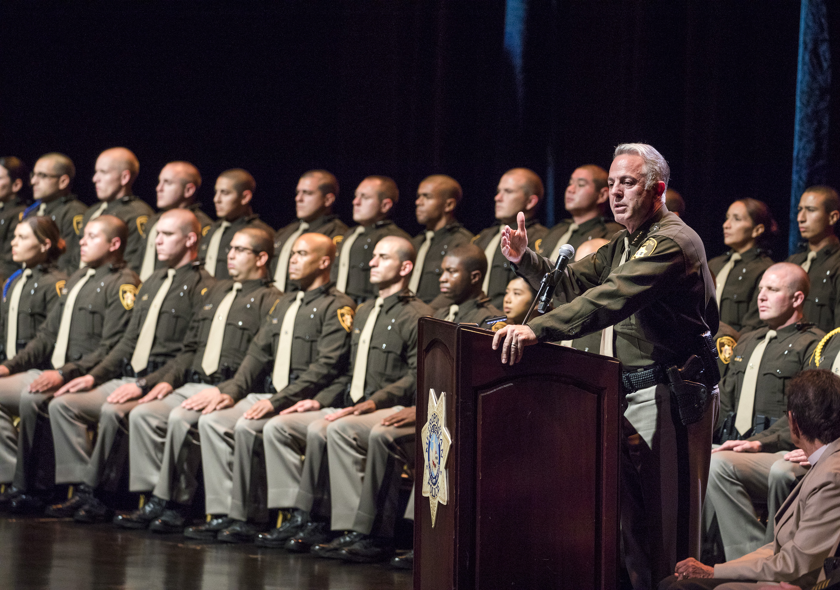 A group of recently graduated police officer sits on stage.