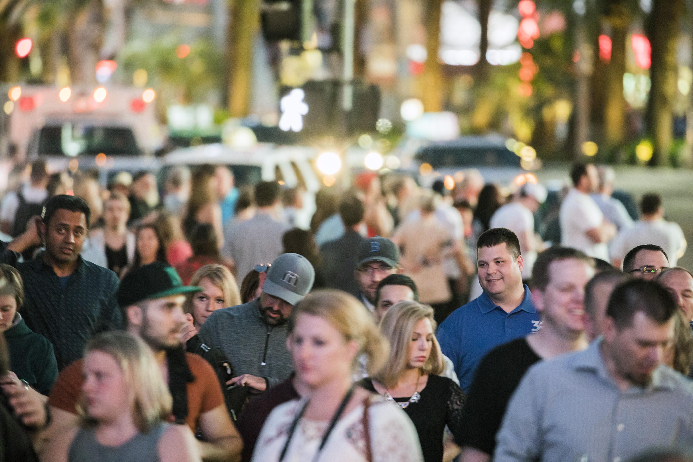 A crowd of people walking down Las Vegas Boulevard