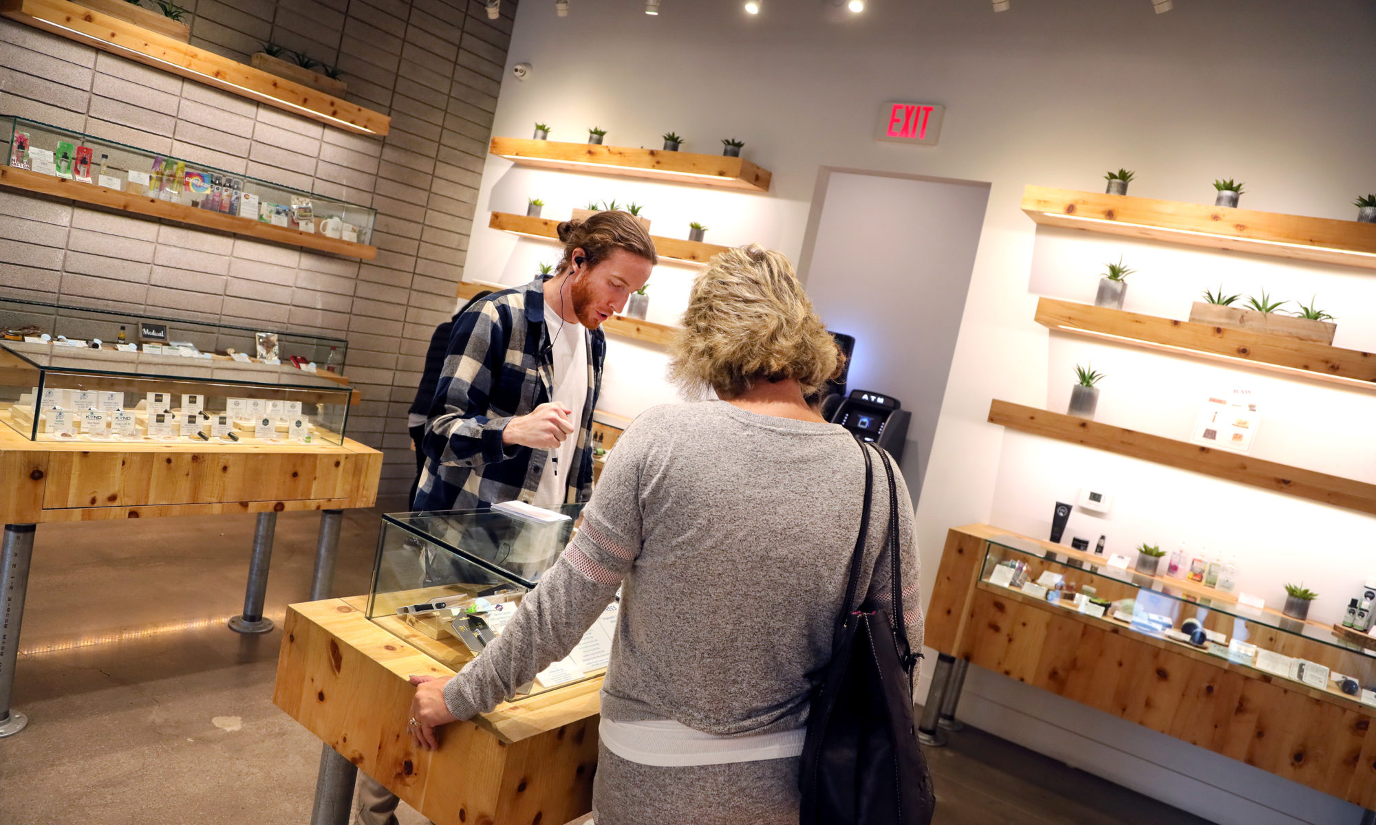 Patient advisor Regan Fueget explains marijuana products on display to a customer at the+source dispensary in Henderson