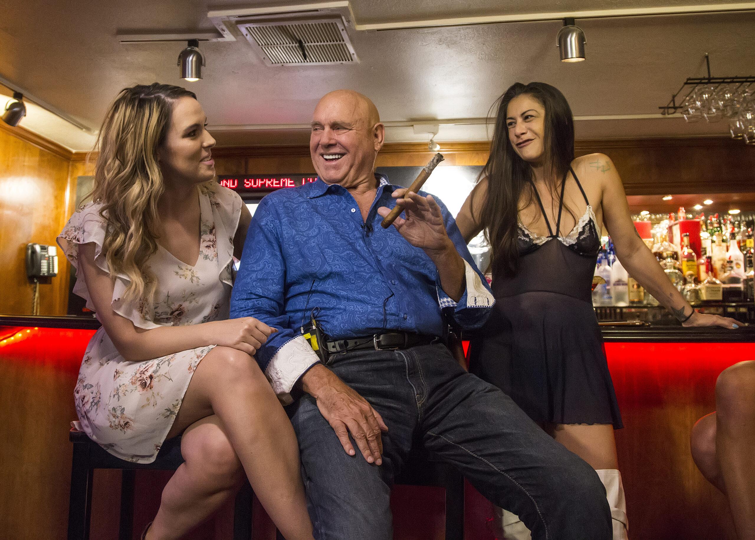 Dennis Hof sits between two women