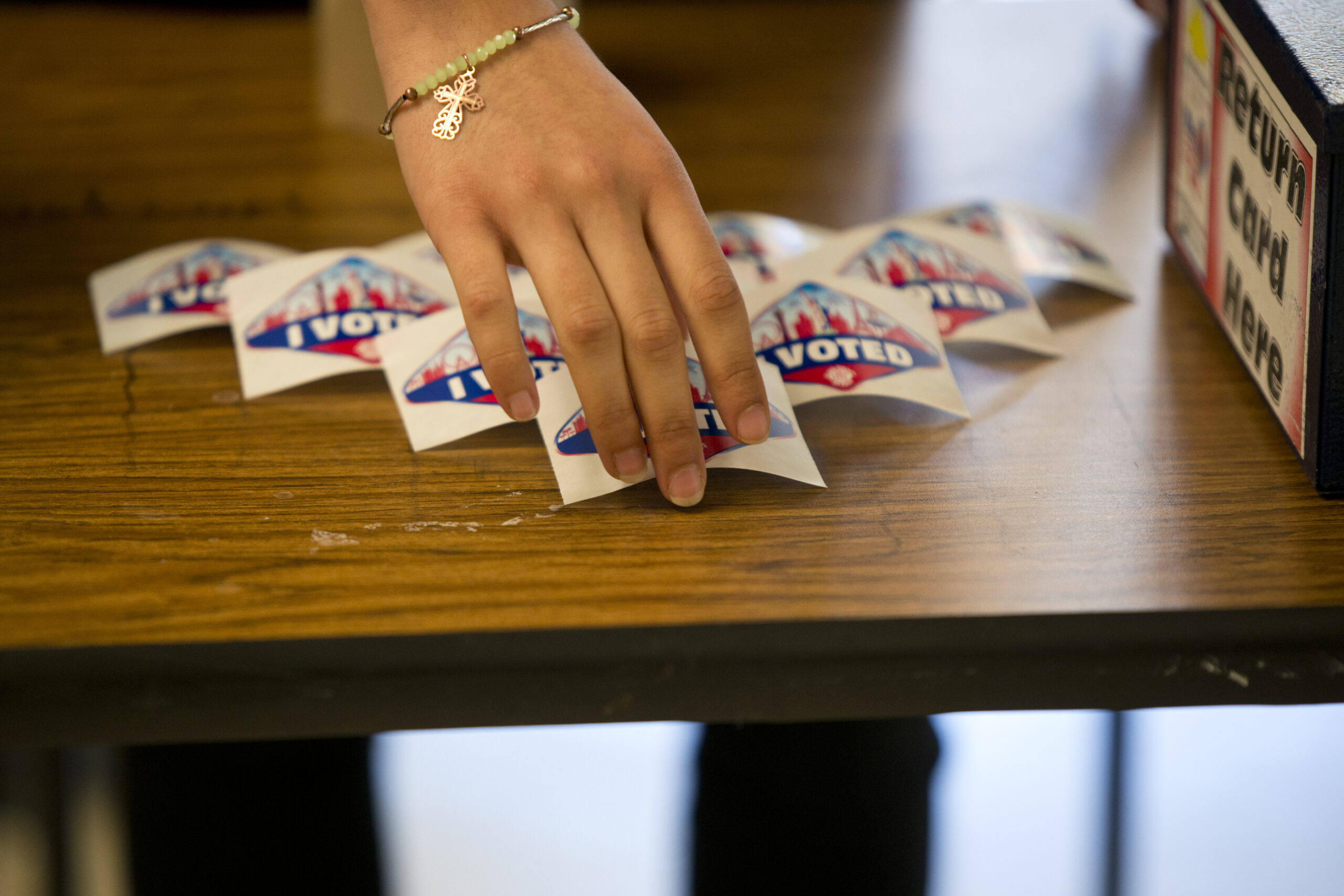 """A hand arranging """"I voted"""" stickers on a table"""