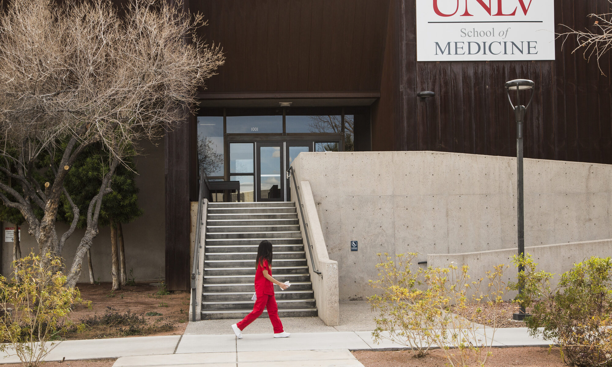 A student walking in front of the UNLV School of Medicine building