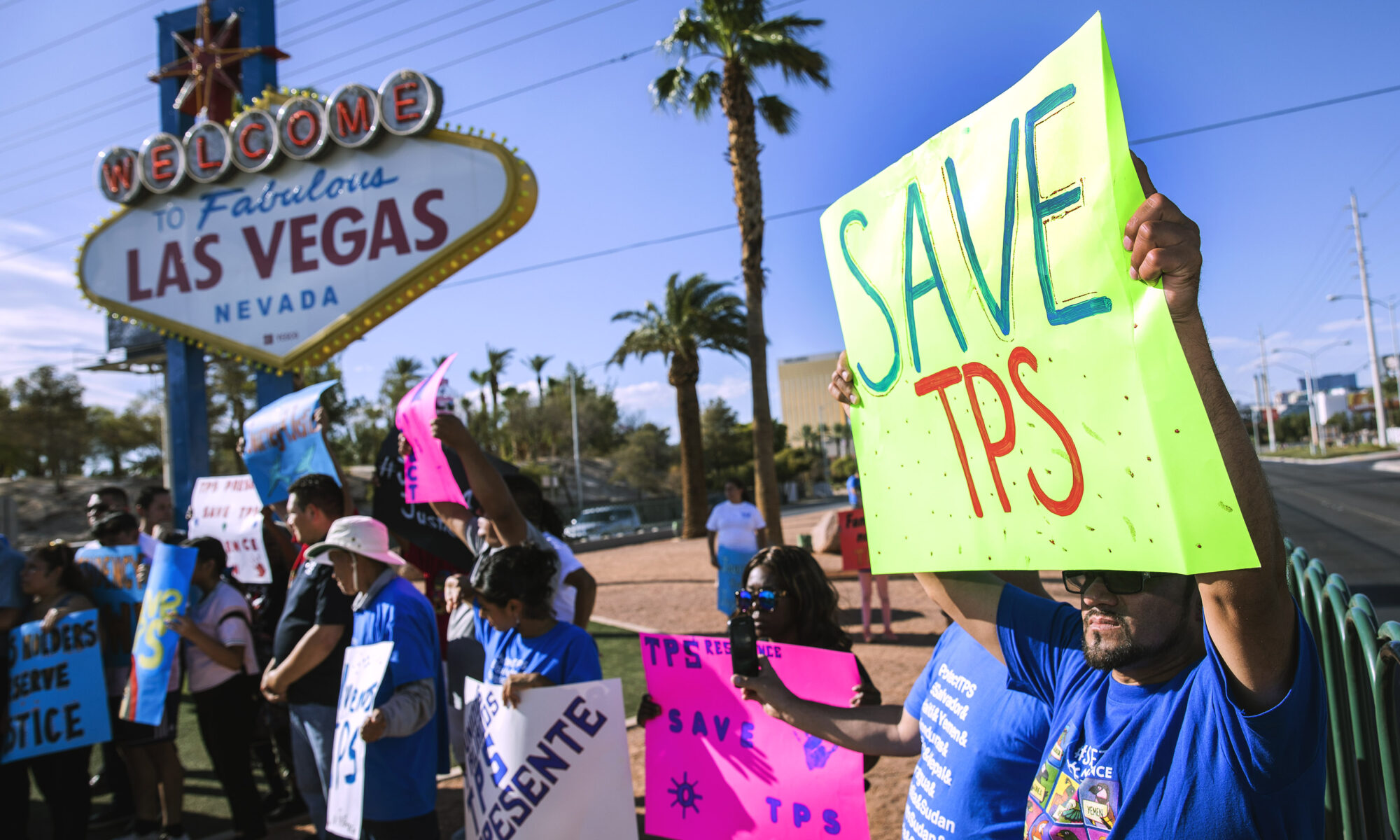 "Protester holding a sign saying ""save TPS"" in front of the Welcome to Las Vegas Sign"