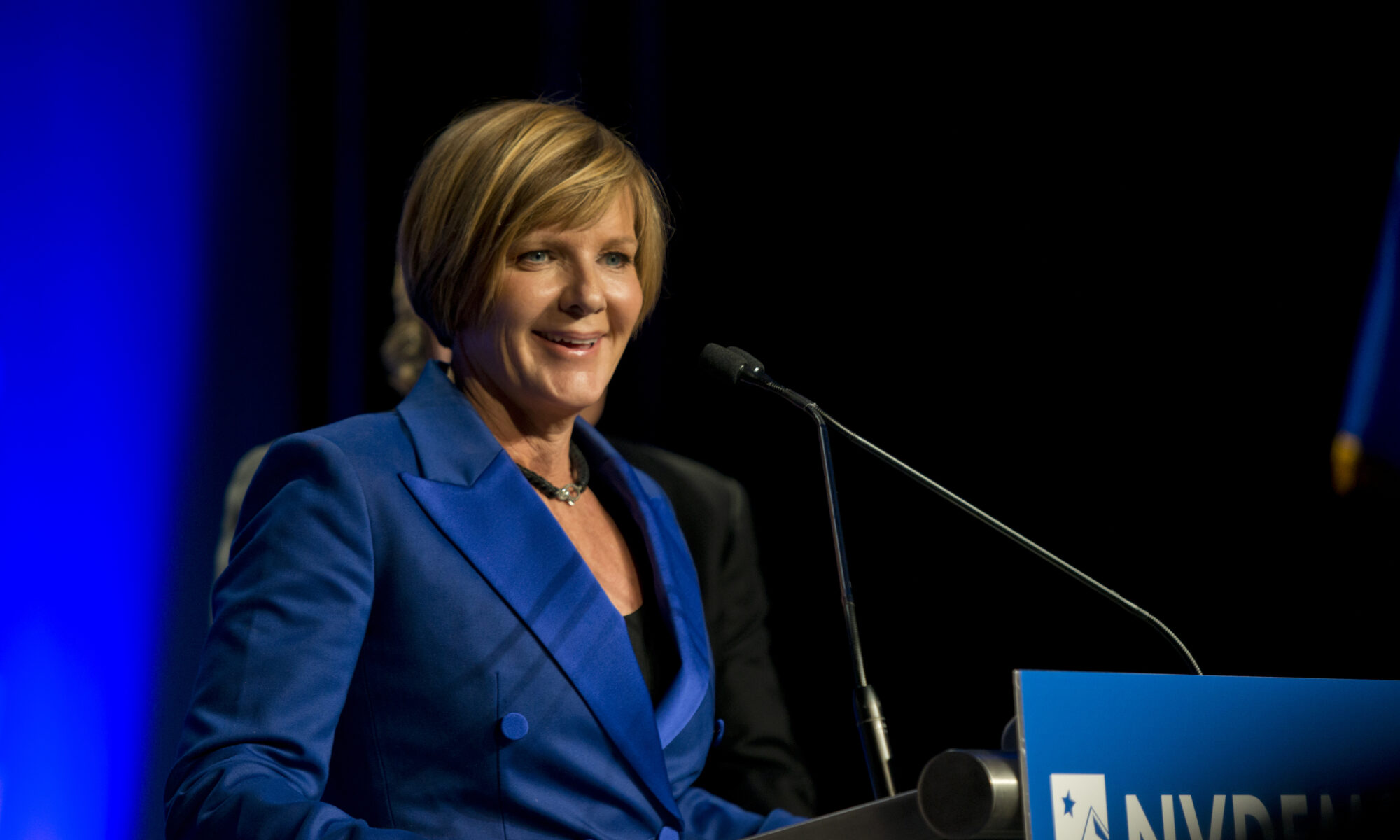 Susie Lee in a blue suit giving a speech