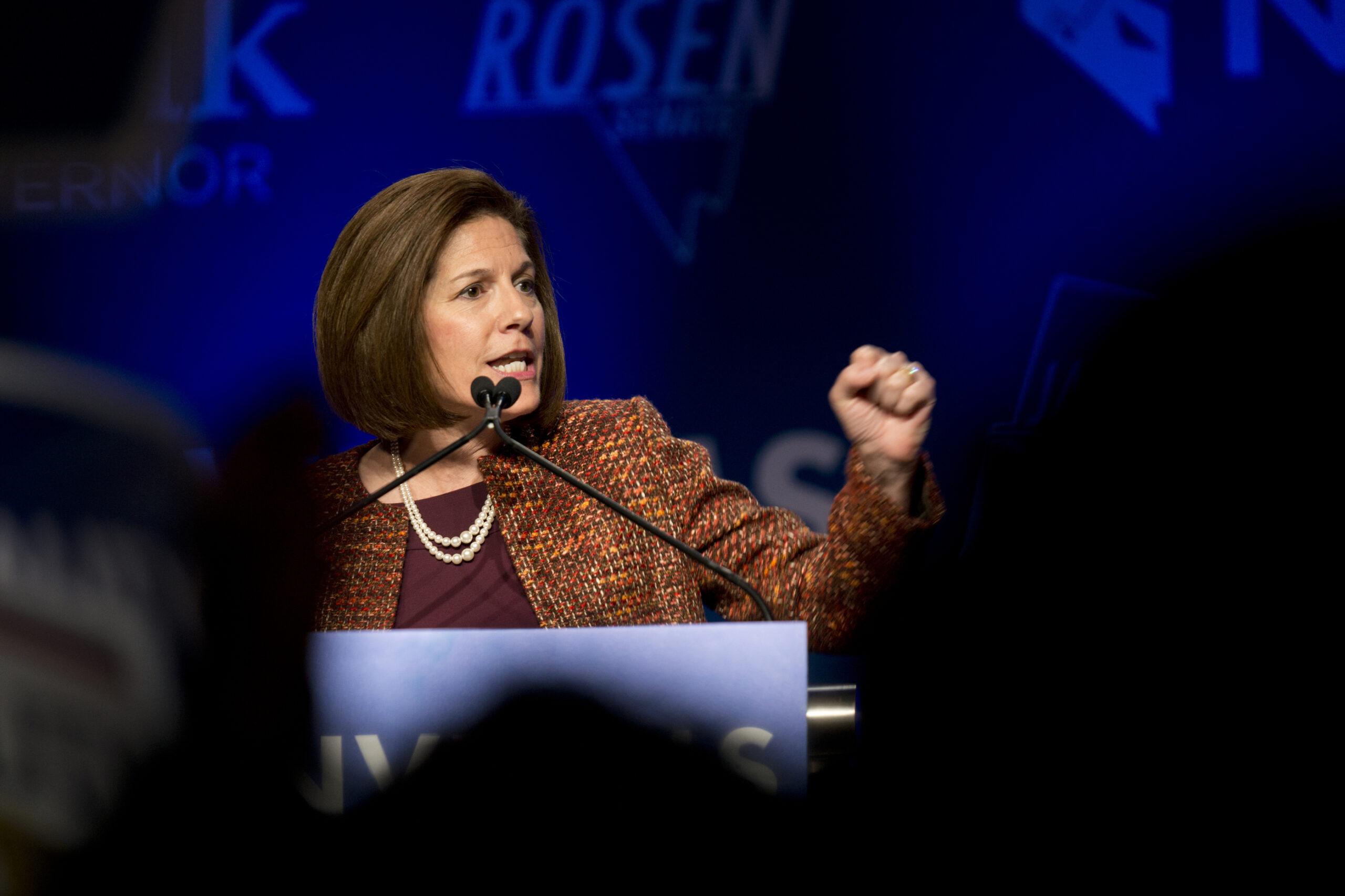 Senator Catherine Cortez Masto speaking into a microphone behind a podium