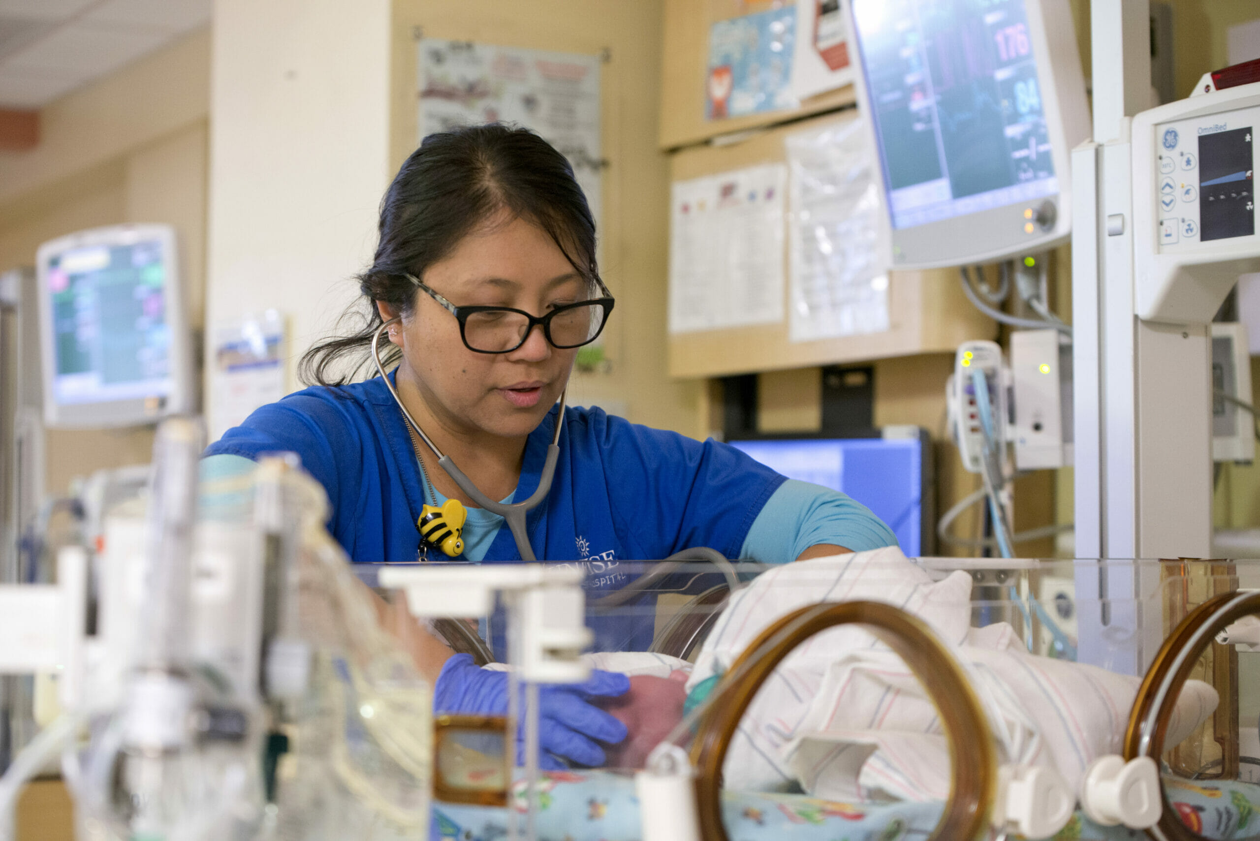 photo of a nurse in blue scrubs leaning over a basinnet