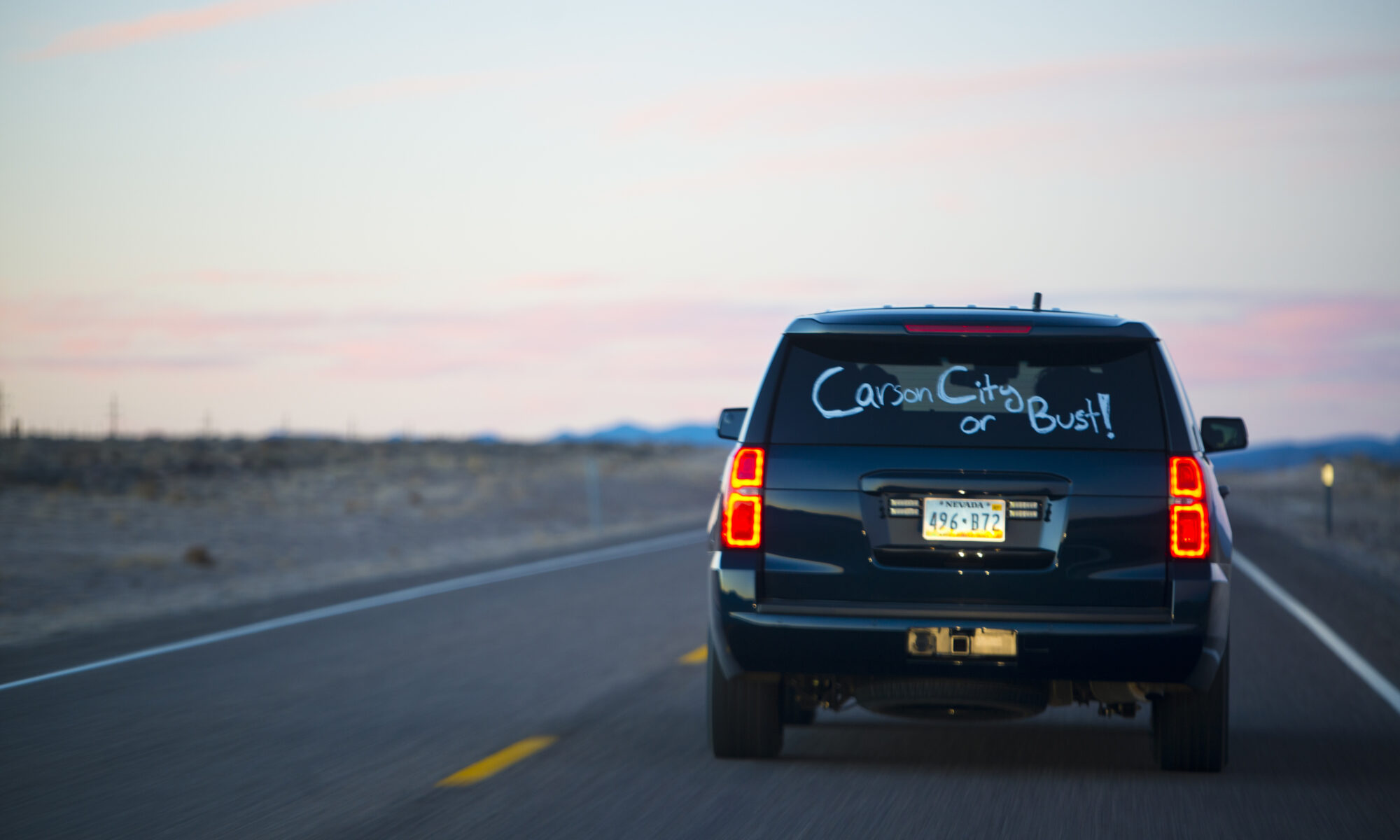 A sport utility vehicle driving on the road at sunset