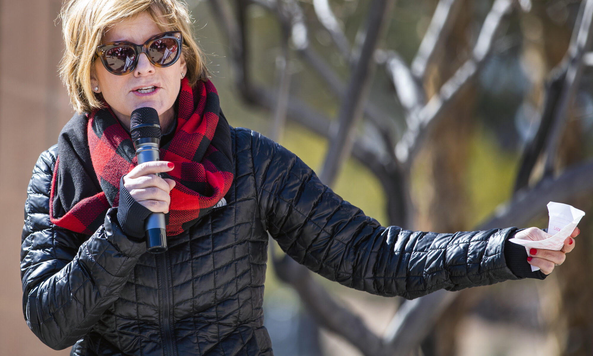 Susie Lee in a jacket and red scarf at an event