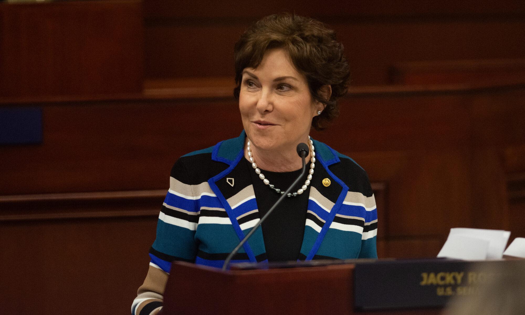 Senator Jacky Rosen in a striped sweater speaking to the Nevada Legislature