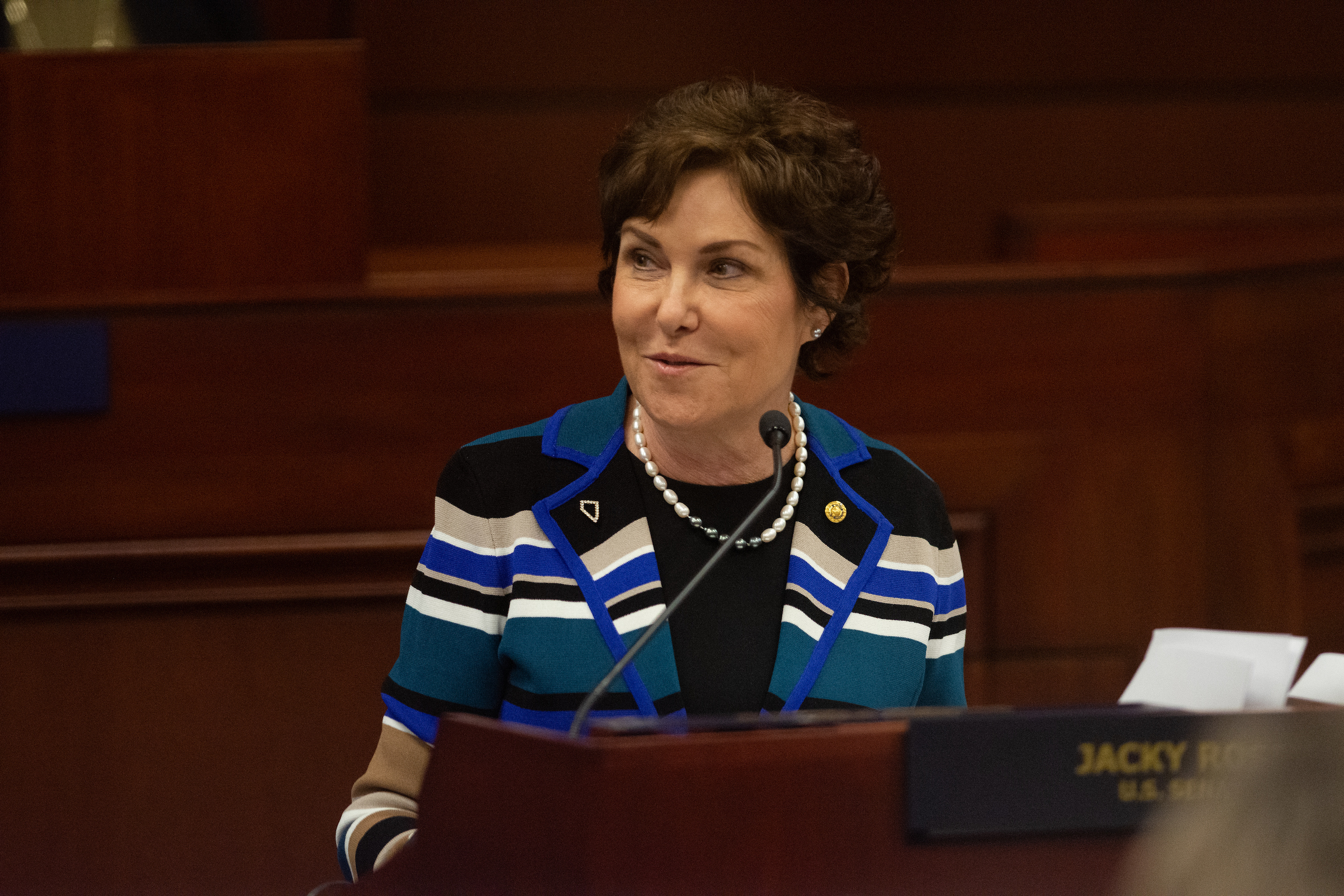 Senator Jacky Rosen in a striped sweater speaking to the Nevada Legislature